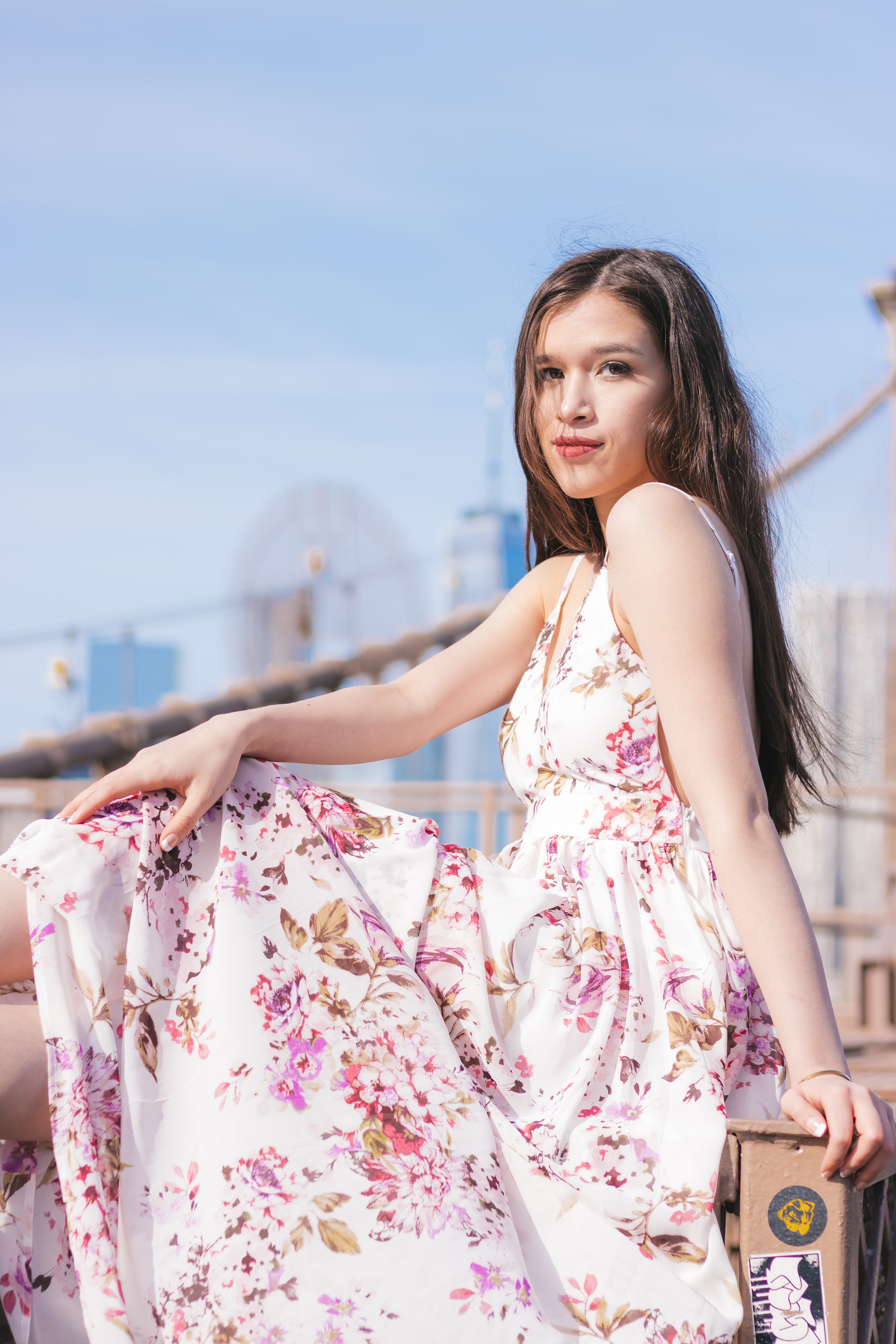 girl woman teenager with long brown hair stilling on the brooklyn bridge with a view of manhattan one world trade center freedom tower in a floral maxi dress backless gown