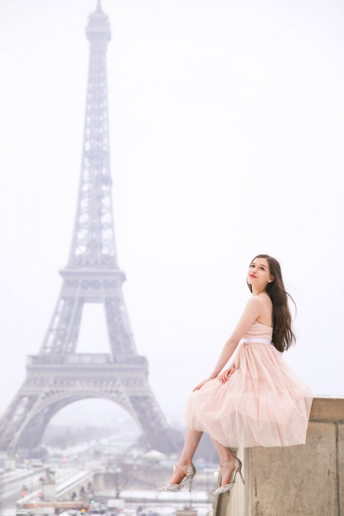 Paris eiffel tower photo inspiration girl long brown hair woman wearing pink tulle dress with white ribbon in the snow snowy photoshoot pink glitter sparkle stilettos heels Blue by Betsey Johnson in Trocadero