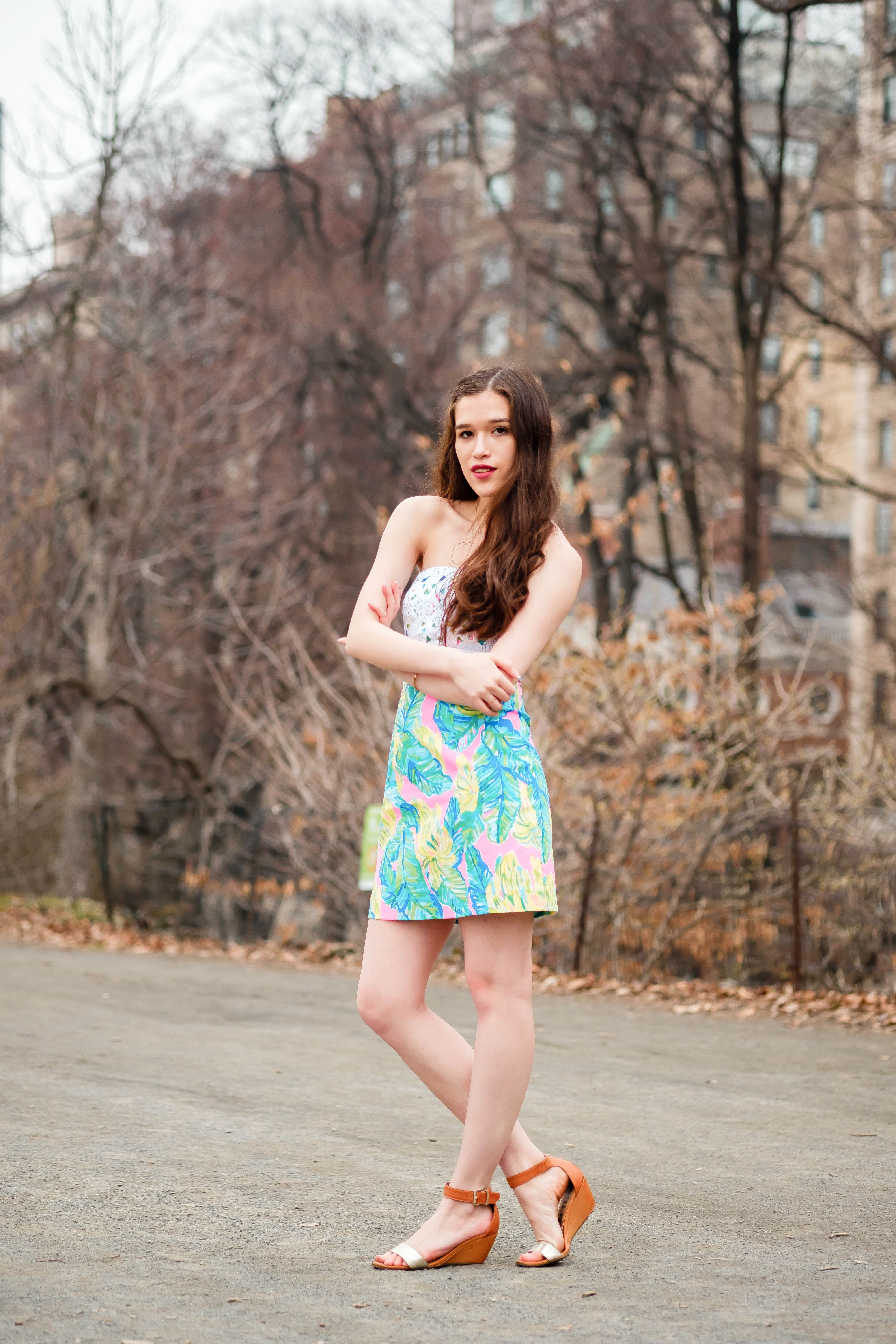 lilly pulitzer preppy girl clothing fashion outfit brynn dress in local flavor pink palm leaf leaves print pattern sundress with white lace girl with long curly brown hair hairstyle curled in central park manhattan nyc new york city gold wedges wedge shoe fashion style trees without leaves on unpaved road