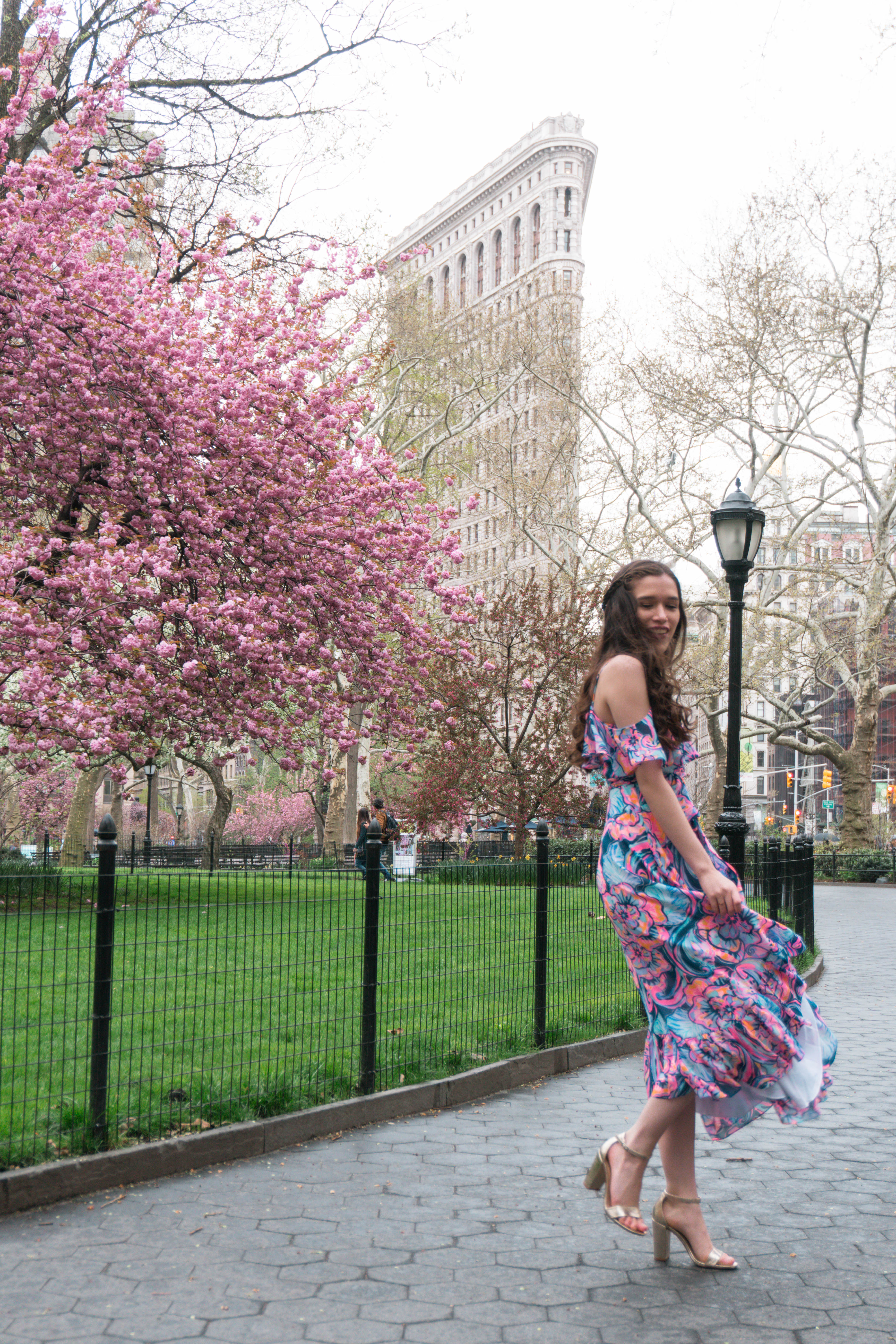 Lilly Pulitzer Marianna Dress in Boho Bateau Outside of the NYC Flatiron Building cherry blossom trees flowering blooms spring new york city wedding guest dress outfit ideas midi floral wrap dress with ruffle long brown hair curled brunette in gold strap metallic chunky heels madison square park may asian american trendy womens fashion inspiration inspo what to wear summer outdoor wedding event party target cheap shoes a new day pink blue purple orange green spinning twirling around movement portrait photography full body vacation