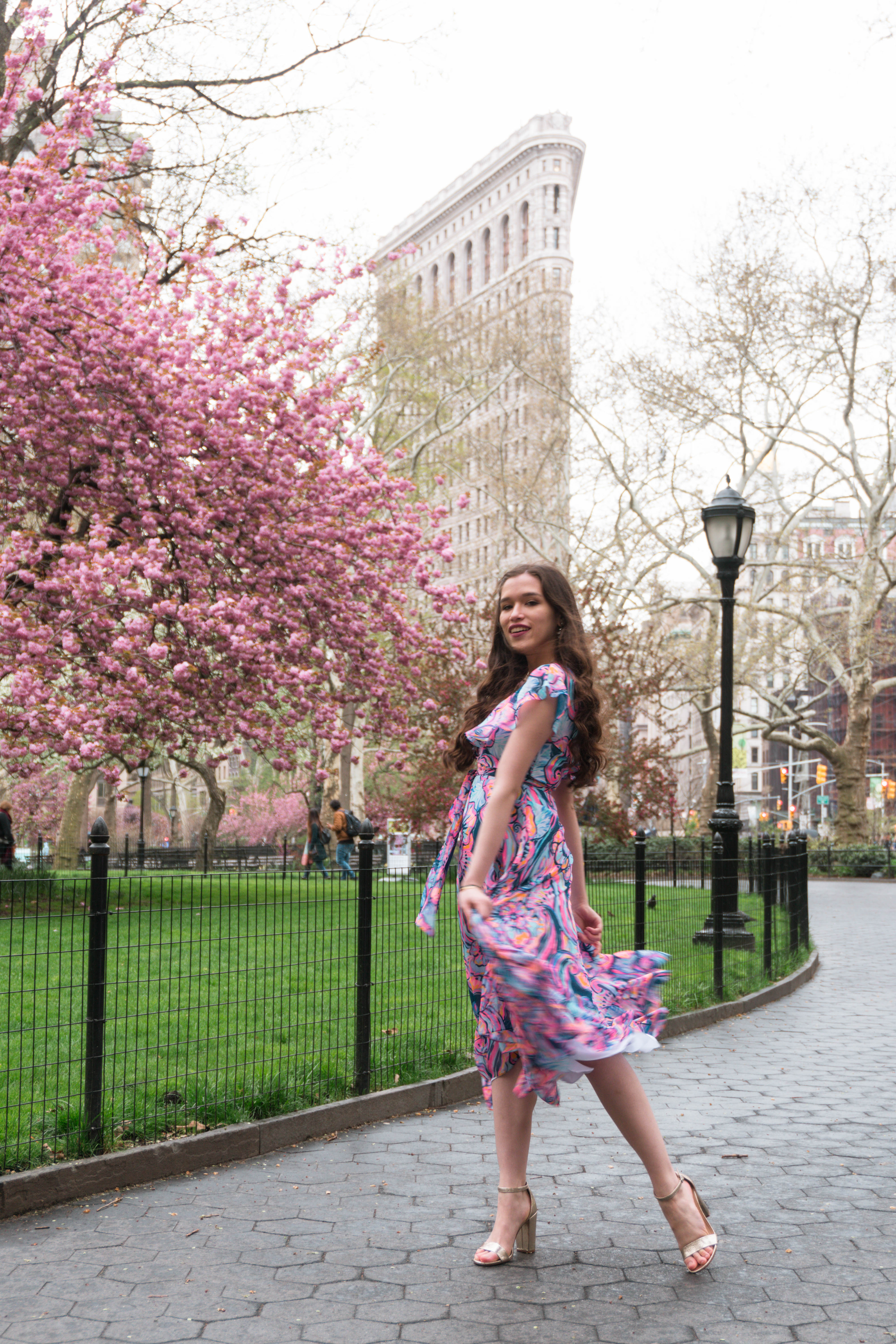 Lilly Pulitzer Marianna Dress in Boho Bateau Outside of the NYC Flatiron Building cherry blossom trees flowering blooms spring new york city wedding guest dress outfit ideas midi floral wrap dress with ruffle long brown hair curled brunette in gold strap metallic chunky heels madison square park may asian american trendy womens fashion inspiration inspo what to wear summer outdoor wedding event party