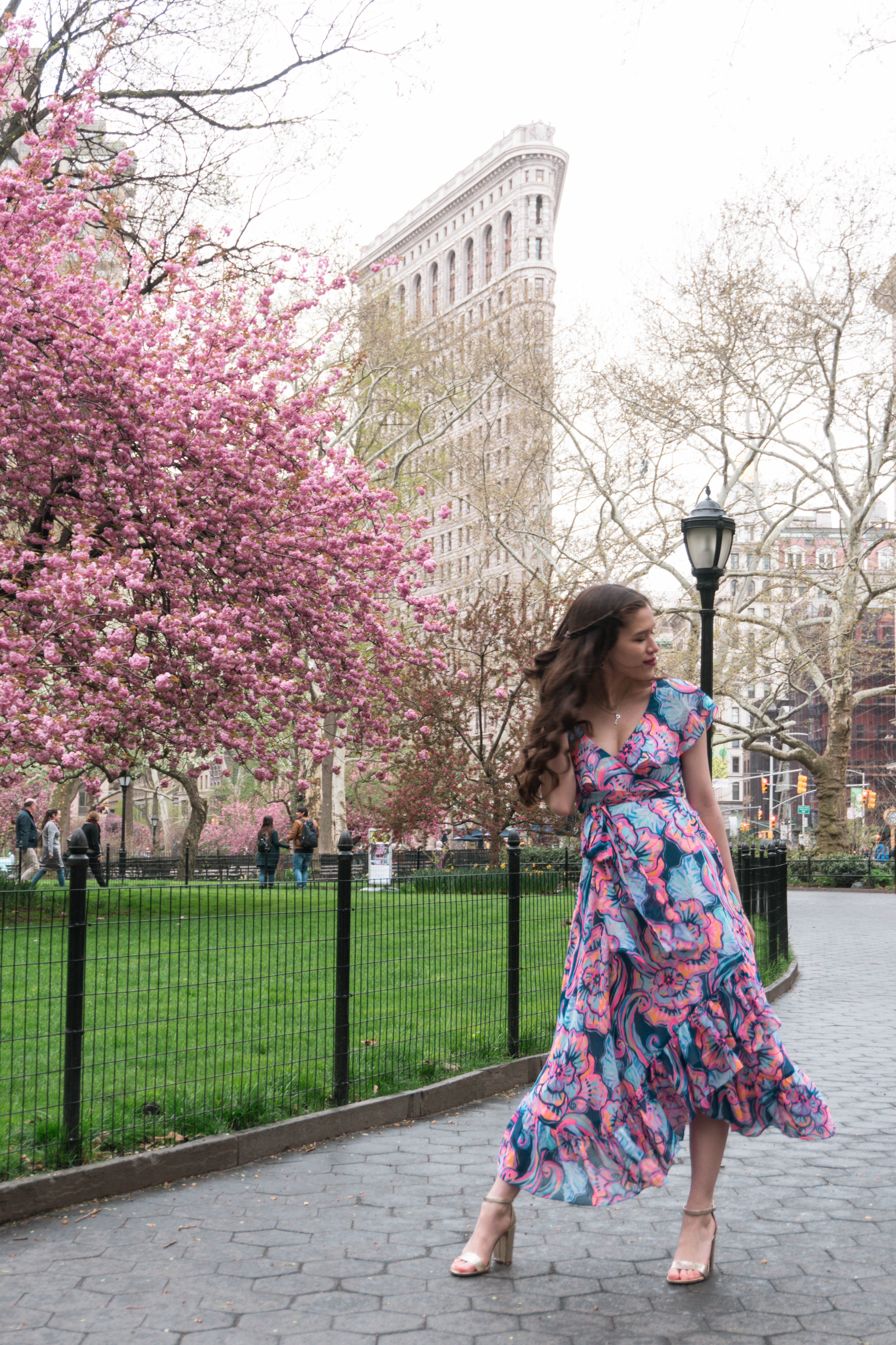 Lilly Pulitzer Marianna Dress in Boho Bateau Outside of the NYC Flatiron Building cherry blossom trees flowering blooms spring new york city wedding guest dress outfit ideas midi floral wrap dress with ruffle long brown hair curled brunette in gold strap metallic chunky heels madison square park may asian american trendy womens fashion inspiration inspo what to wear summer outdoor wedding event party target cheap shoes a new day pink blue purple orange green