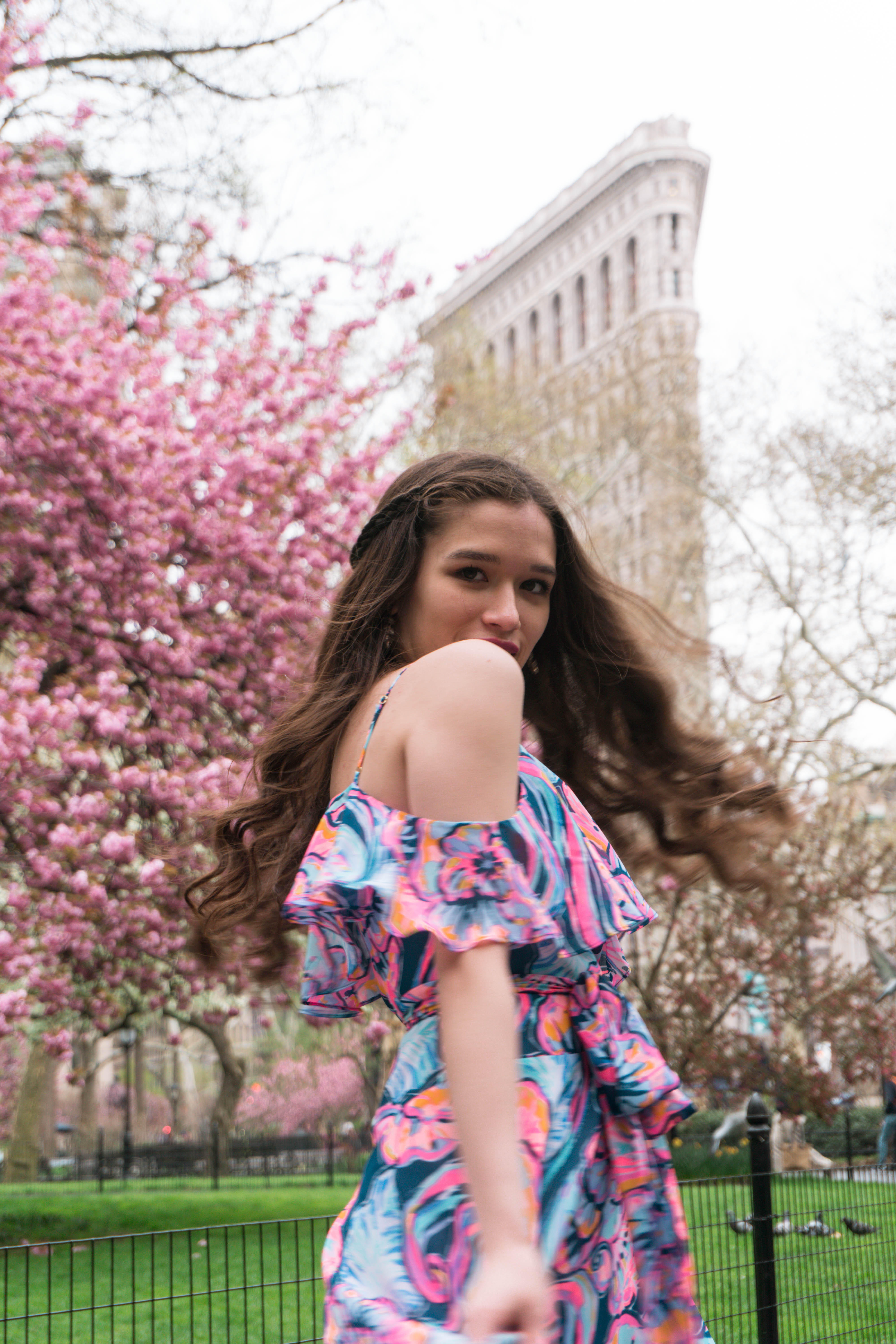 Lilly Pulitzer Marianna Dress in Boho Bateau Outside of the NYC Flatiron Building cherry blossom trees flowering blooms spring new york city wedding guest dress outfit ideas midi floral wrap dress with ruffle long brown hair curled brunette in gold strap metallic chunky heels madison square park may asian american trendy womens fashion inspiration inspo what to wear summer outdoor wedding event party target cheap shoes a new day pink blue purple orange green spinning twirling around movement portrait photography