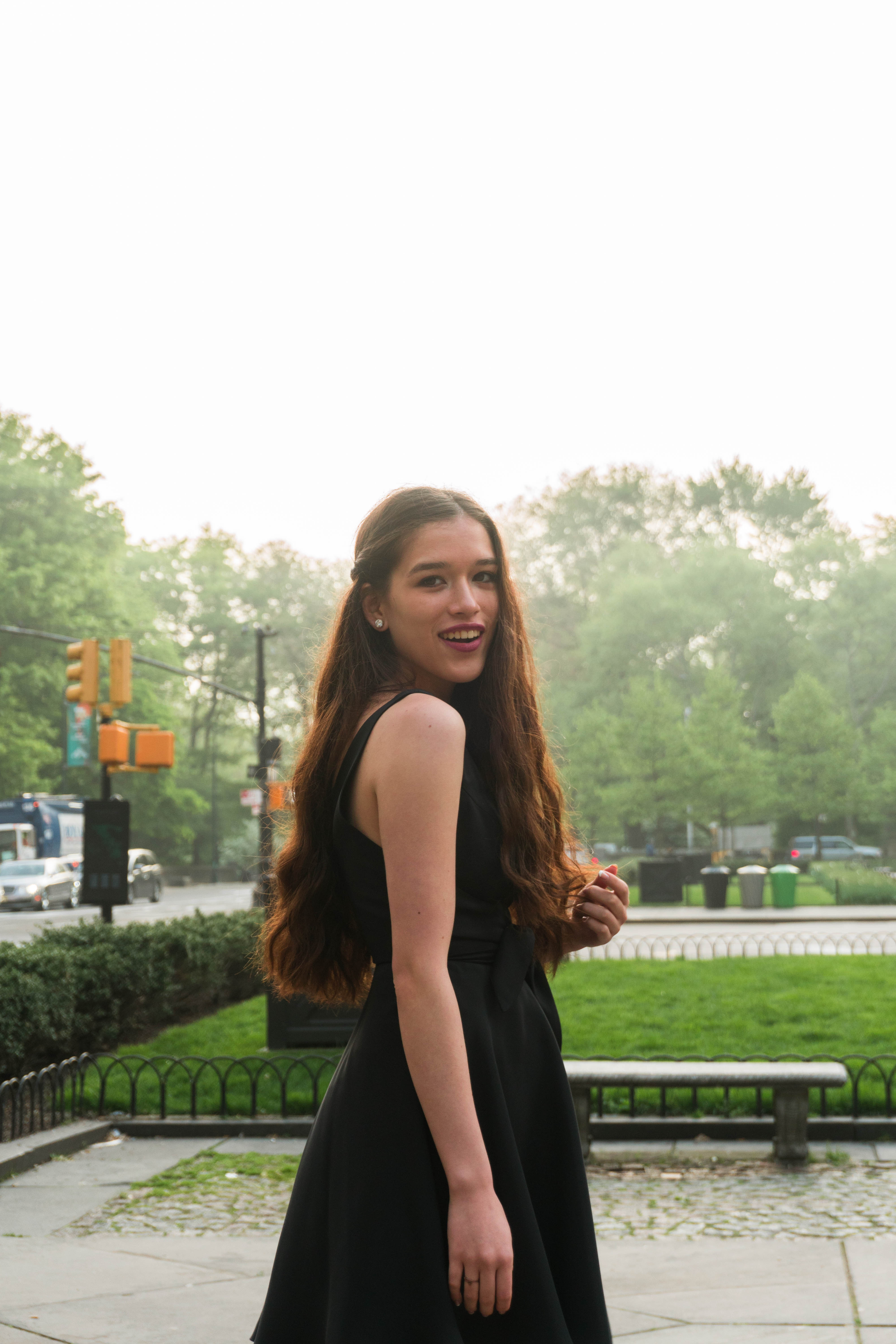 Amanda Uprichard little black dress classic style in NYC New York City Manhattan Central Park by the Plaza Hotel teenager teen girl woman with long brown wavy hair loose curls summer wedding guest style silk black sundress