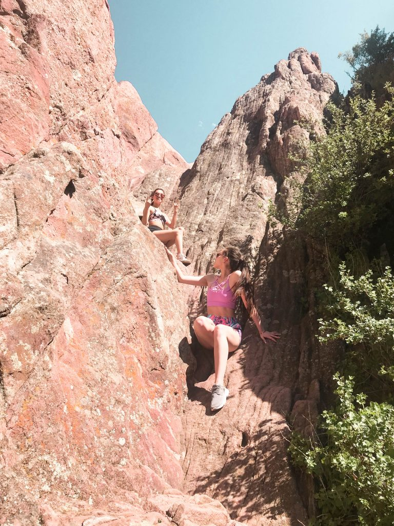 boulder colorado travel with me travel vlog what to do in the southwest girl with long brown hair in wrapped ponytail sitting on red rocks Lilly Pulitzer runaround run around short shorts in boho bateau victoria's secret VS pink sports bra luxletic navy sperry seven 7 seas luxletic two girls climing on red rocks rock climbing hiking athletic adventure destination for fit physical activity outdoor fashion what to wear on a hike asian american hapa caucasian