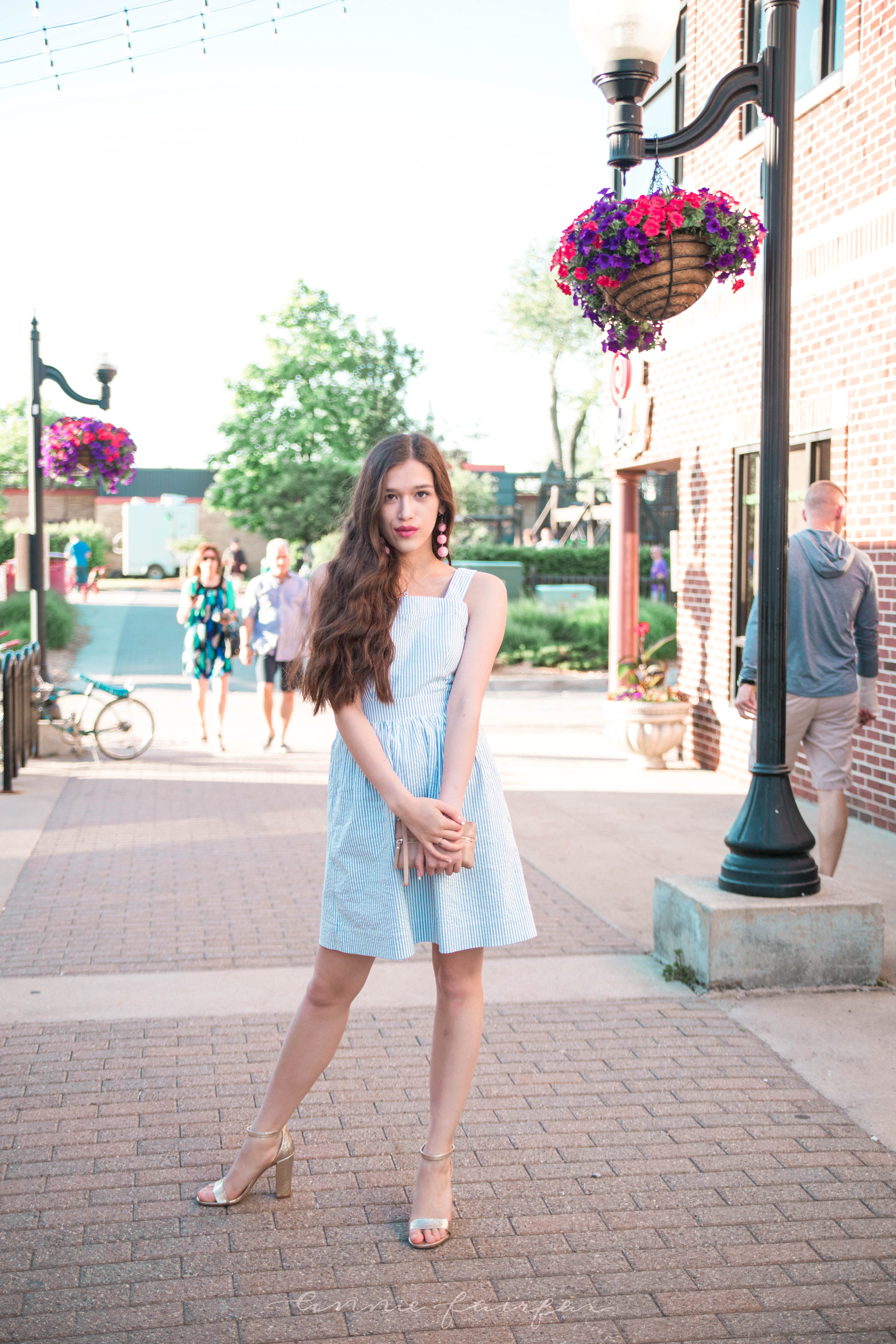 j. crew jcrew factory blue and white seersucker minidress fit and flare dress with pockets above the knee gold metallic chunky heels long brown wavy hair girl standing on sidewalk preppy style flattering for any body type