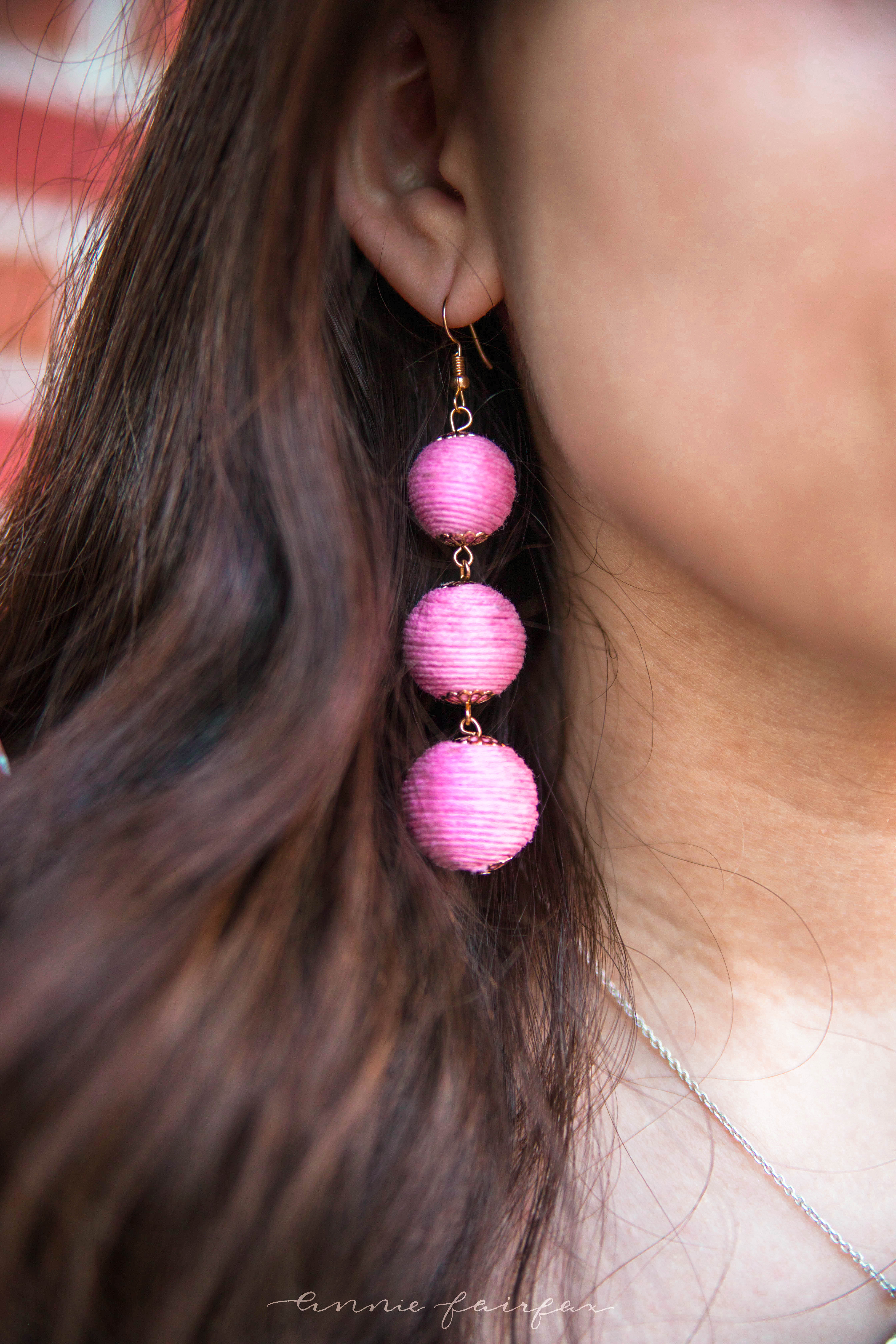 girl with brown hair detail shot light bright pink ball drop earrings with thread preppy accessories classic quirky jewelry
