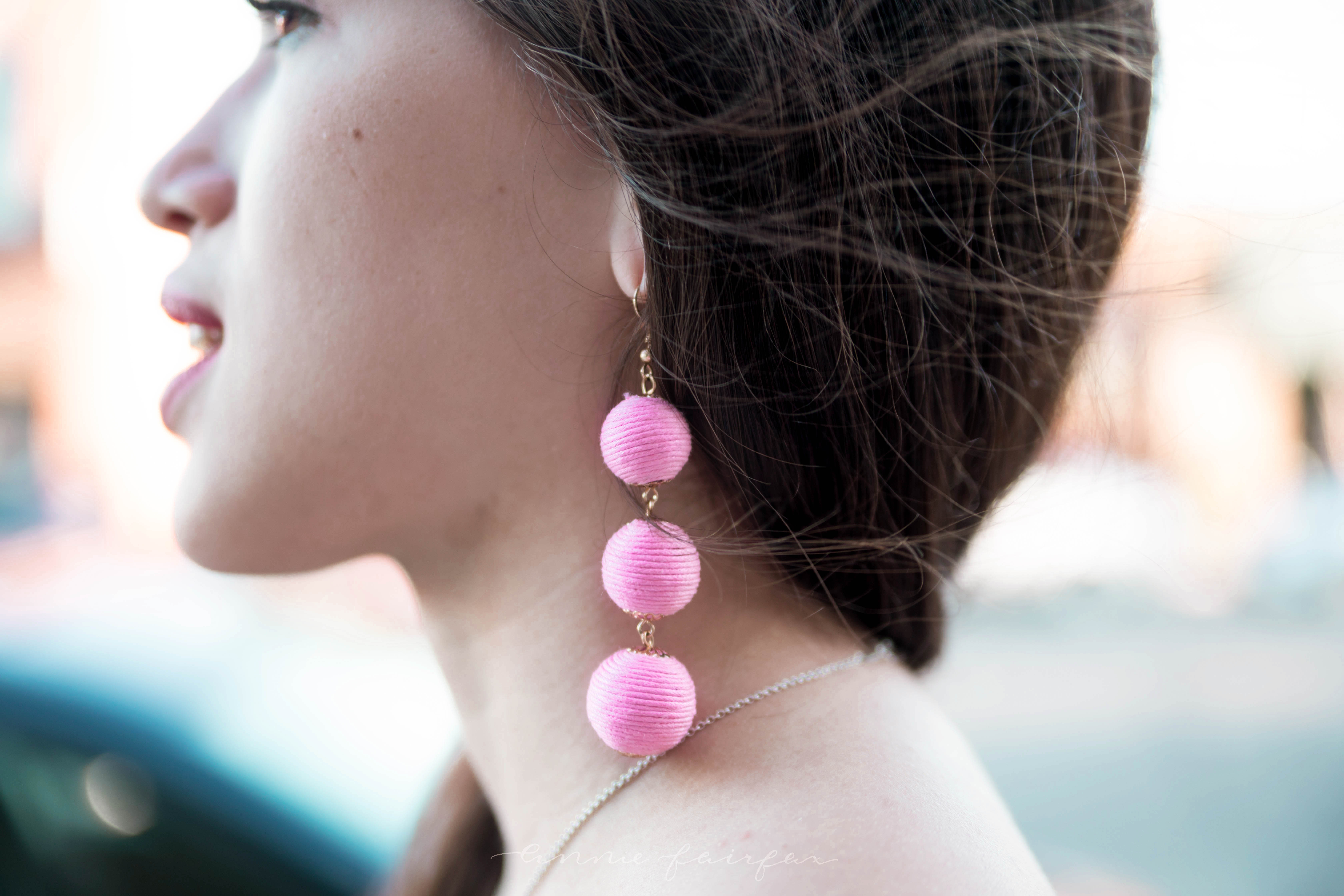 girl with brown hair detail shot light bright pink ball drop earrings with thread preppy accessories classic quirky jewelry profile view mod