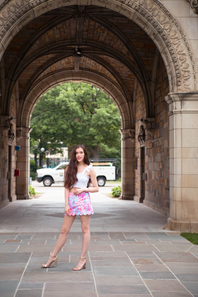 national wear your lilly day lilly pulitzer preppy girl style in ann arbor michigan pink printed scallop skort white smocked crop top with bow tie knot straps colette skort in aquadesiac University of Michigan gold metallic chunky block heels comfortable girl standing in archway tunnel with long brown hair