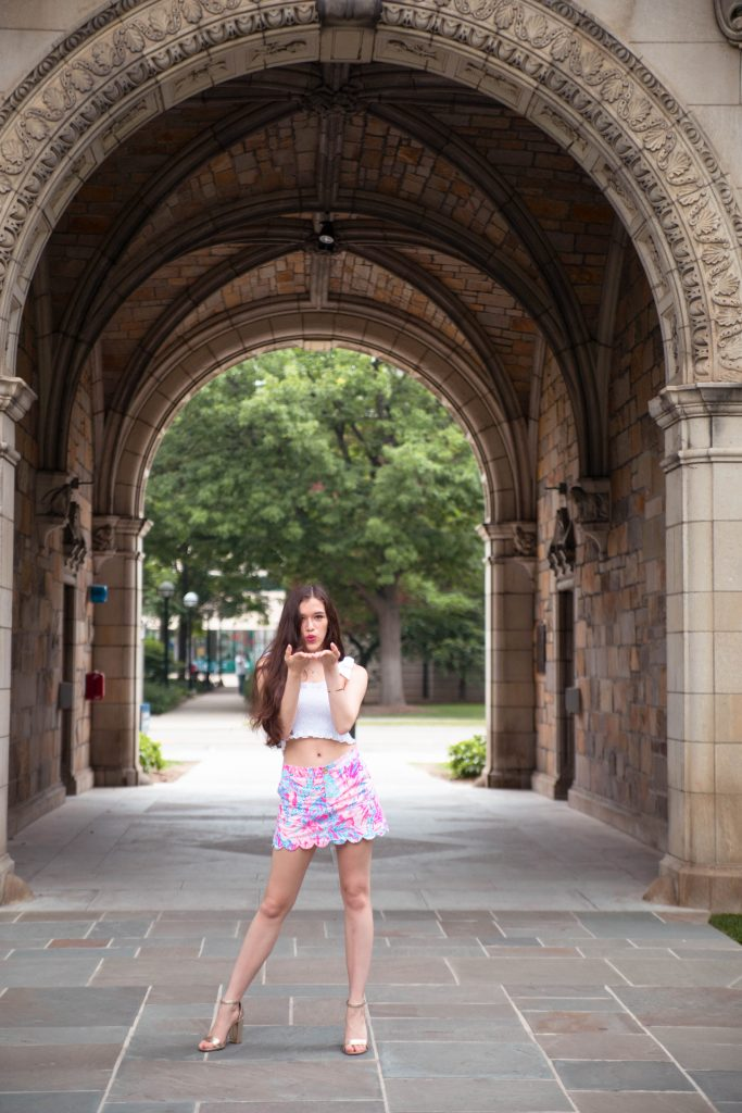 national wear your lilly day lilly pulitzer preppy girl style in ann arbor michigan pink printed scallop skort white smocked crop top with bow tie knot straps colette skort in aquadesiac University of Michigan gold metallic chunky block heels comfortable girl standing in archway tunnel with long brown hair blowing a kiss