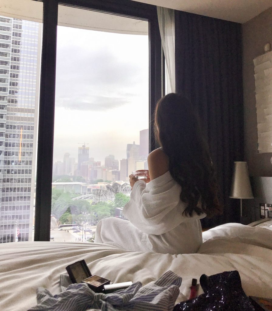 Millenium Park Chicago Radisson Blu Aqua executive business class suite girl with curled long brown hair and white robe sitting on white duvet luxury upper upscale