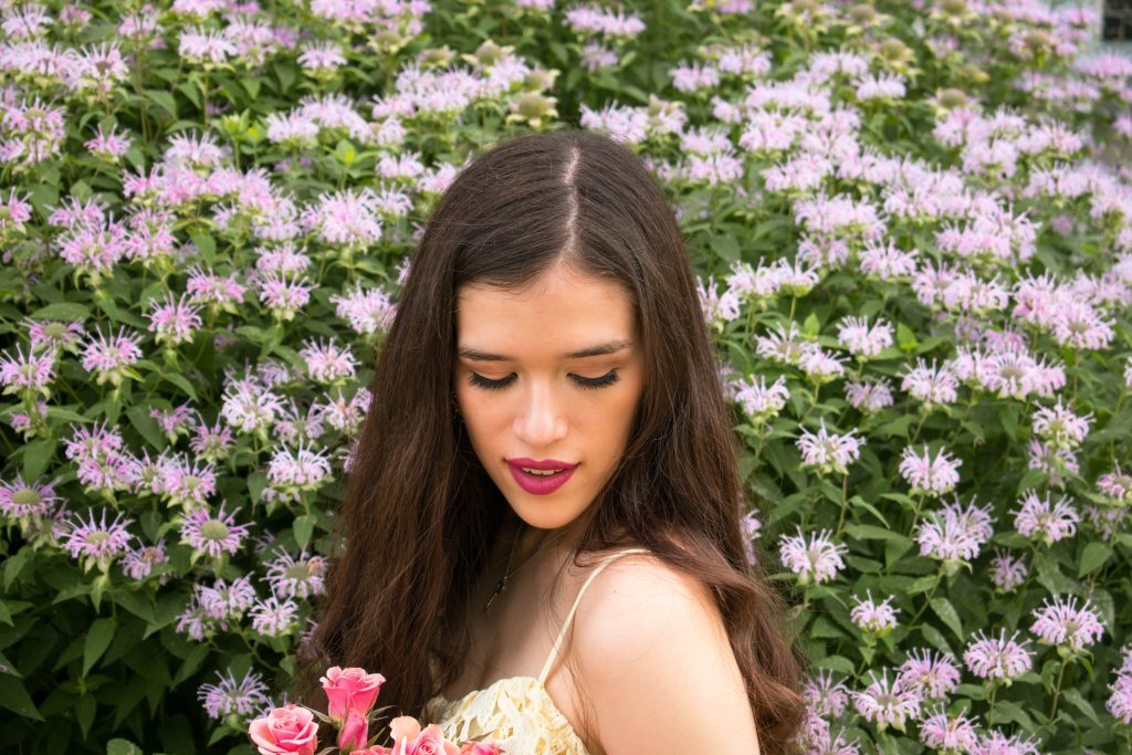 NYC style and fashion blogger Eva Phan of Eva Darling in ASTR the Label yellow lace off the shoulder midi dress from nordstrom wedding guest dress idea summer ootd pale pastel bouquet of roses long brown curled hair brunette how to wear a midi tea length dress inspiration beauty natural makeup glowy skin purple flowers
