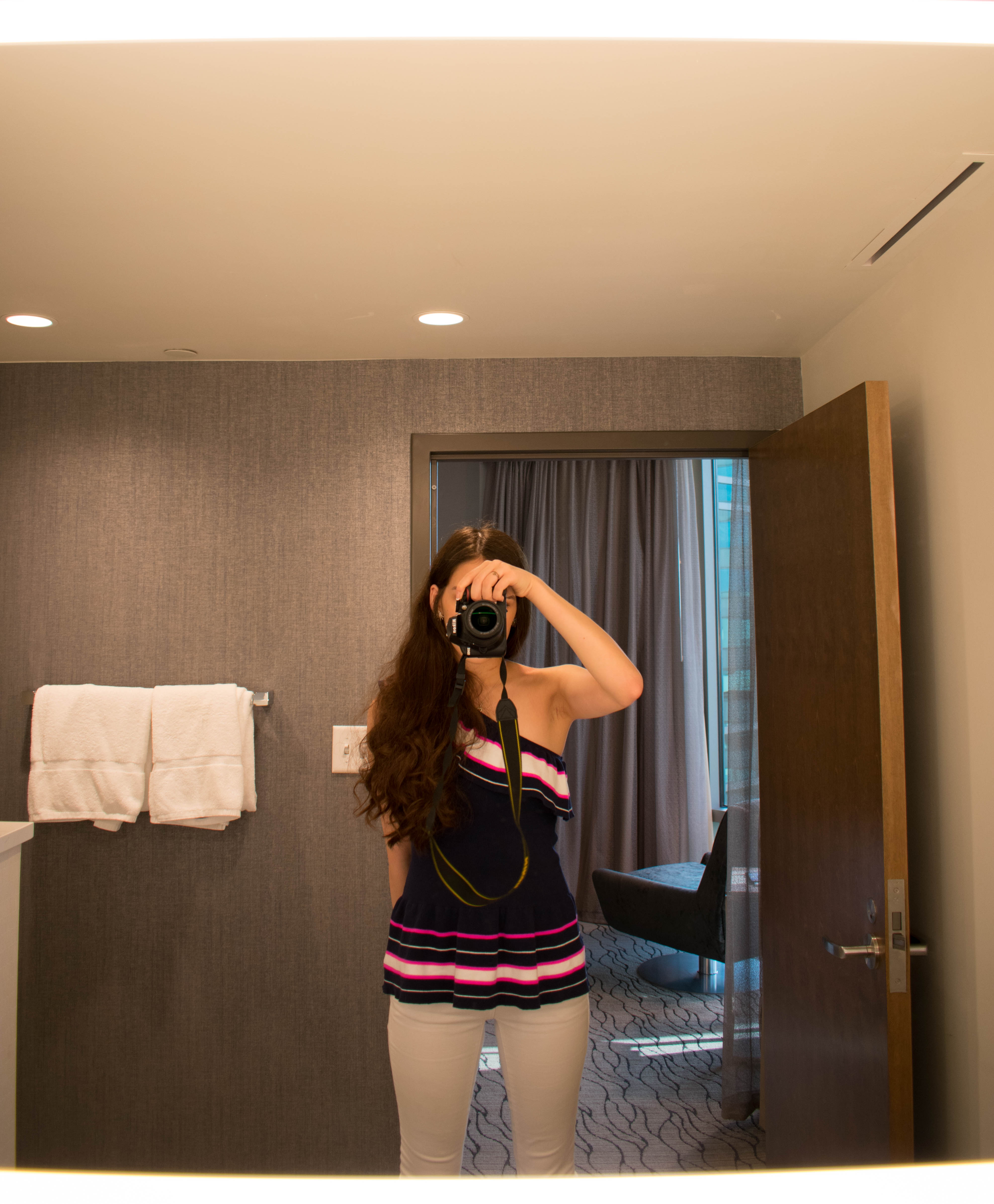 Eva Phan of Eva Darling midwest Minnesota travel blogger in a Lilly Pulitzer mandarina top white vineyard vines skinny jeans holding nikon d3400 DSLR camera in mystic lake casino luxury hotel review prior lake mn