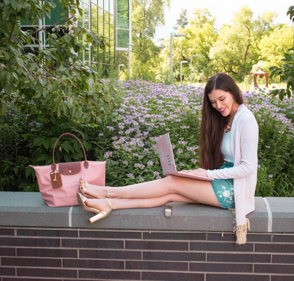 NYC style and college blogger Eva Phan of Eva Darling with longchamp cherry blossom pink le pliage primark denim embroidered skirt lilly pulitzer gold tatum cardigan macbook pro 15 inch gold metallic comfortable target chunky block heels purple flowers laptop