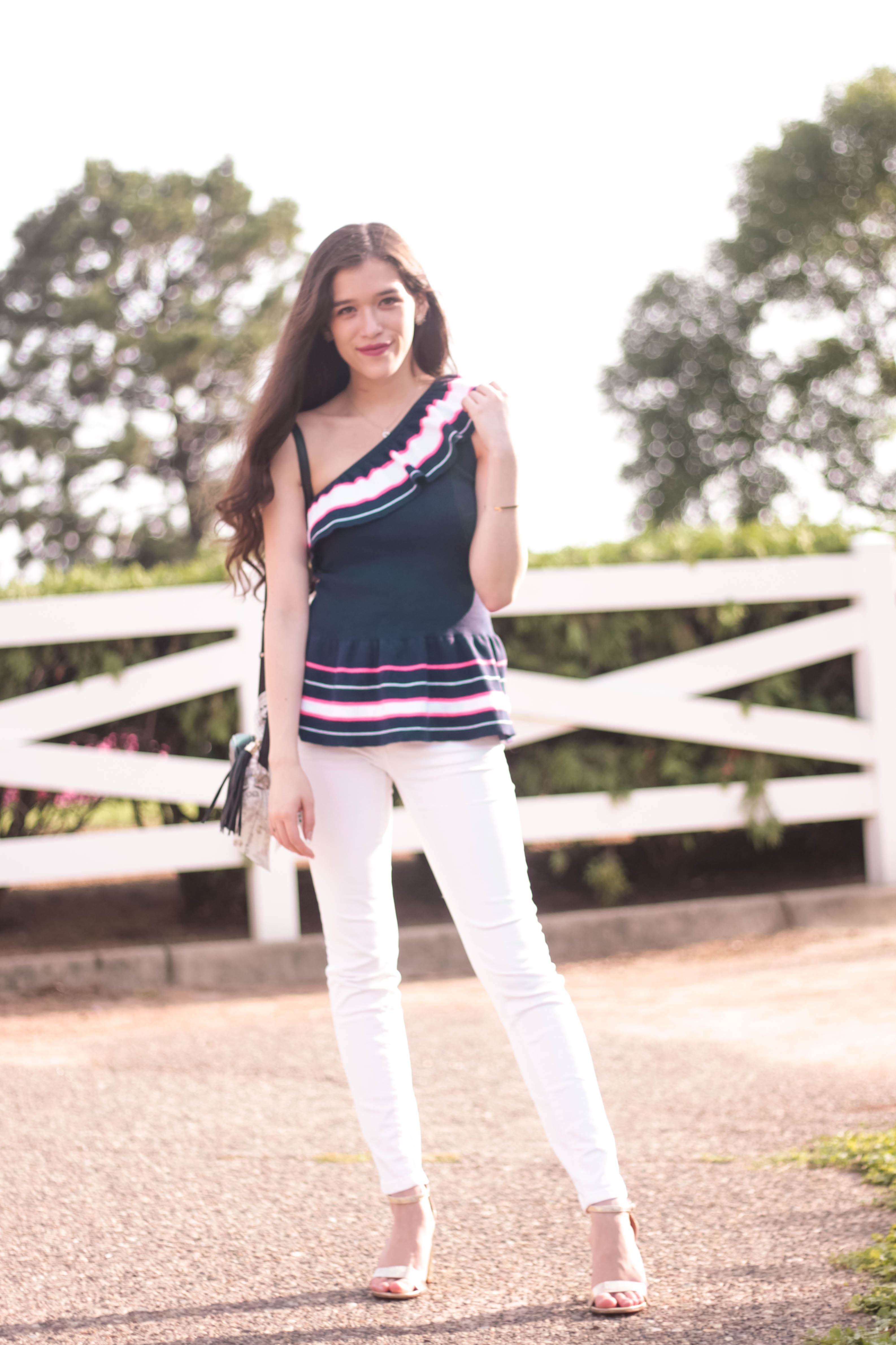 Minnesota Canterbury Park girl with long brown hair wearing white Vineyard Vines skinny denim jeans Lilly Pulitzer navy ruffle asymmetrical one shoulder Mandarina Top and metallic gold chunky heels with black Gucci Soho Disco and Dior Mitzvah Tarot Twilly