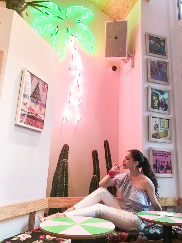 NYC fashion, style, and travel blogger Eva Phan of Eva Darling sitting at Cha Cha Matcha on Broadway in NoMad in a Vineyard Vines seersucker ruffle asymmetrical top, white skinny jeans, and gold comfortable affordable block heel sandals