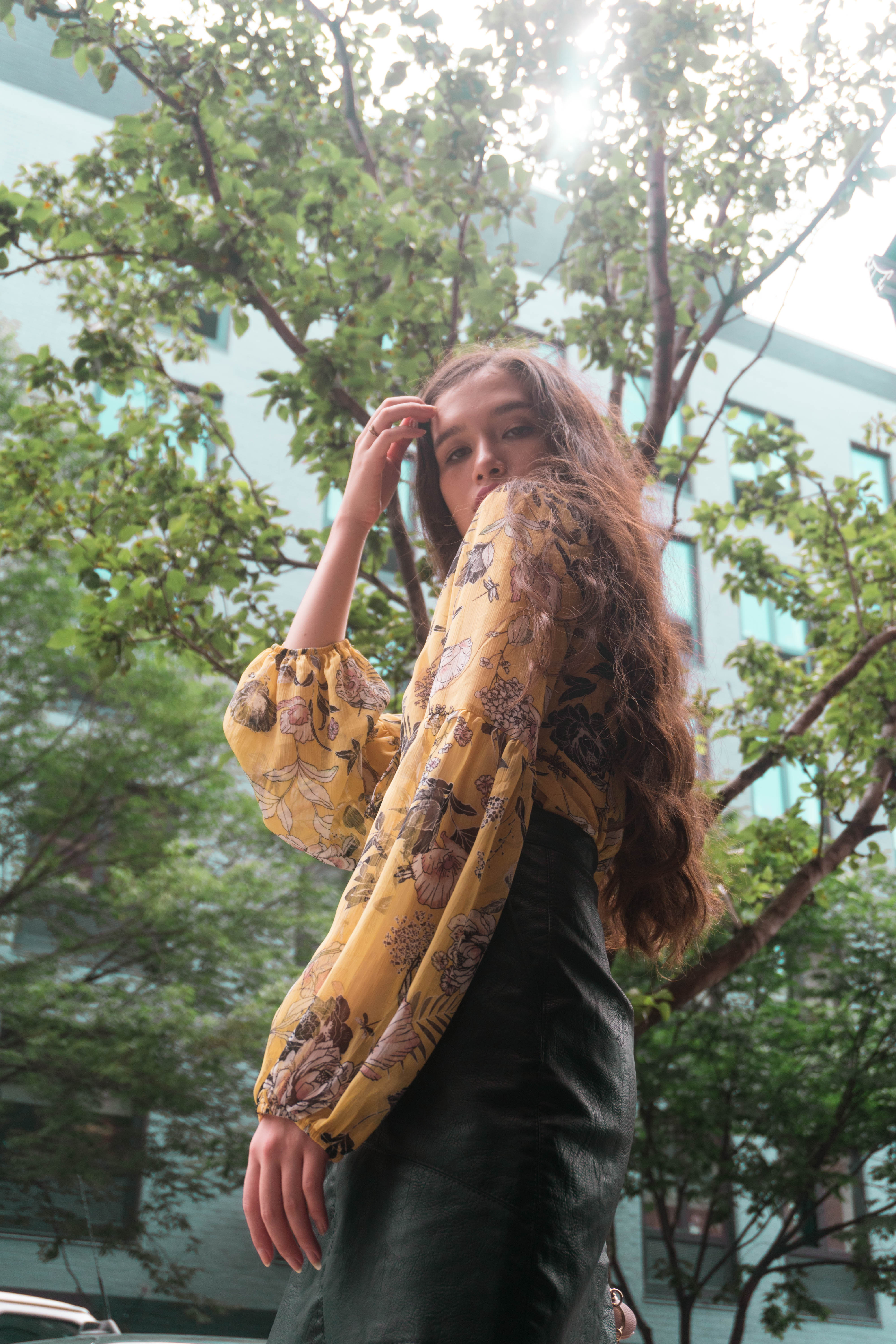 Fashion blogger Eva Phan wearing yellow floral chiffon lantern sleeve top from Target Style and black faux leather mini skirt from Zara in Alphabet City in the East Village in Manhattan girl with long thick hair brunette brown curled with curling wand