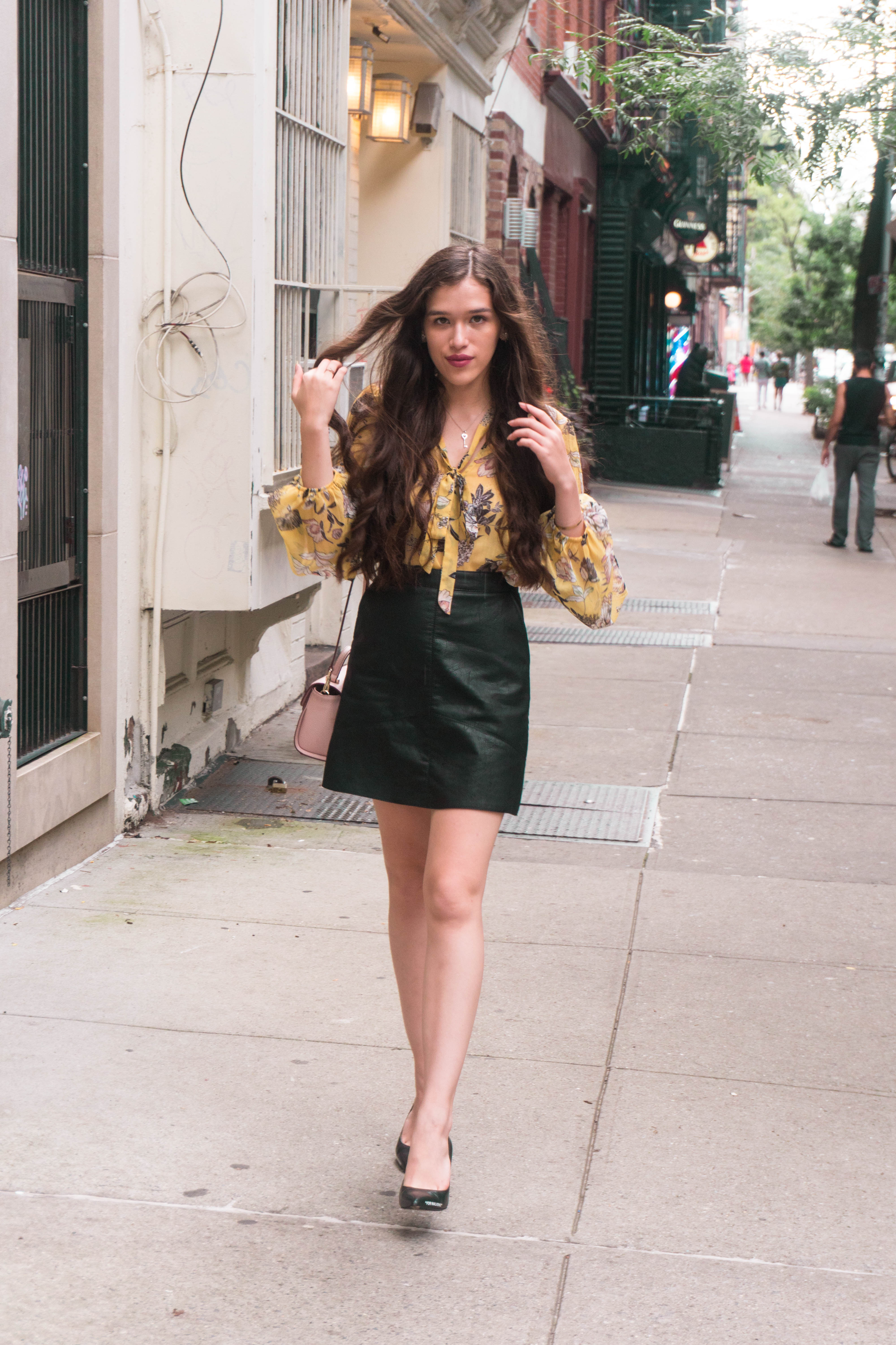 Style Blogger Eva Phan stylish workwear business attire casual office outfit pussy bow chiffon blouse with lantern sleeves yellow pink floral print black faux leather miniskirt from zara fall fashion inspiration girl with long brown thick hair curled pink kate spade makayla bag day to night fashion east village manhattan nyc alphabet city sitting off white c/o virgil abloh for walking heels pumps walking down sidewalk