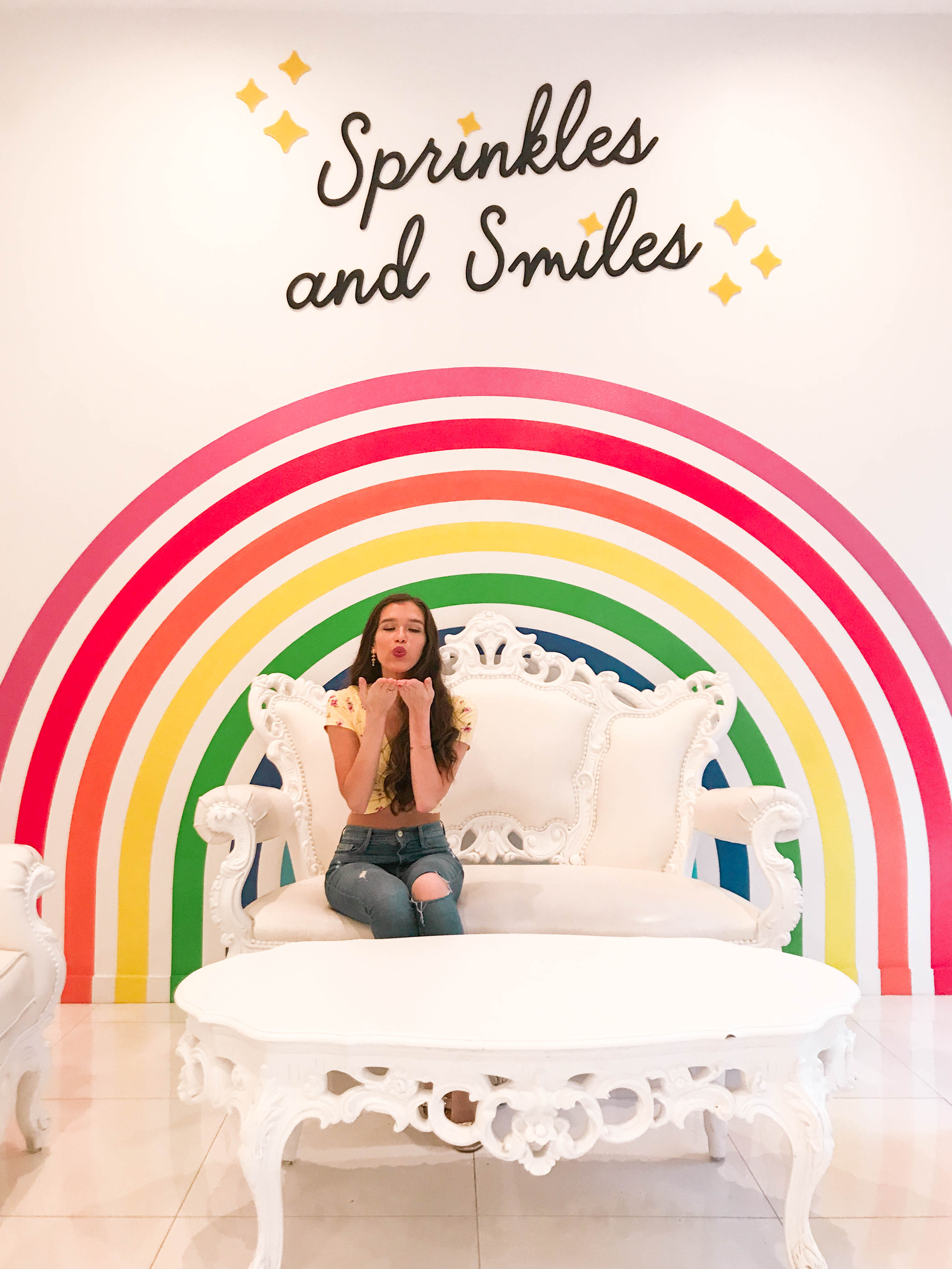 Travel and Style blogger Eva Phan of Eva Darling shares the most Instagram worthy bakeries in SoHo wearing a yellow floral twist front crop top from forever 21, frame denim high waisted forever karlie jeans, and gucci marmont city metallic gold sandals at flour shop in soho nyc manhattan. Colorful wall mural in New York City