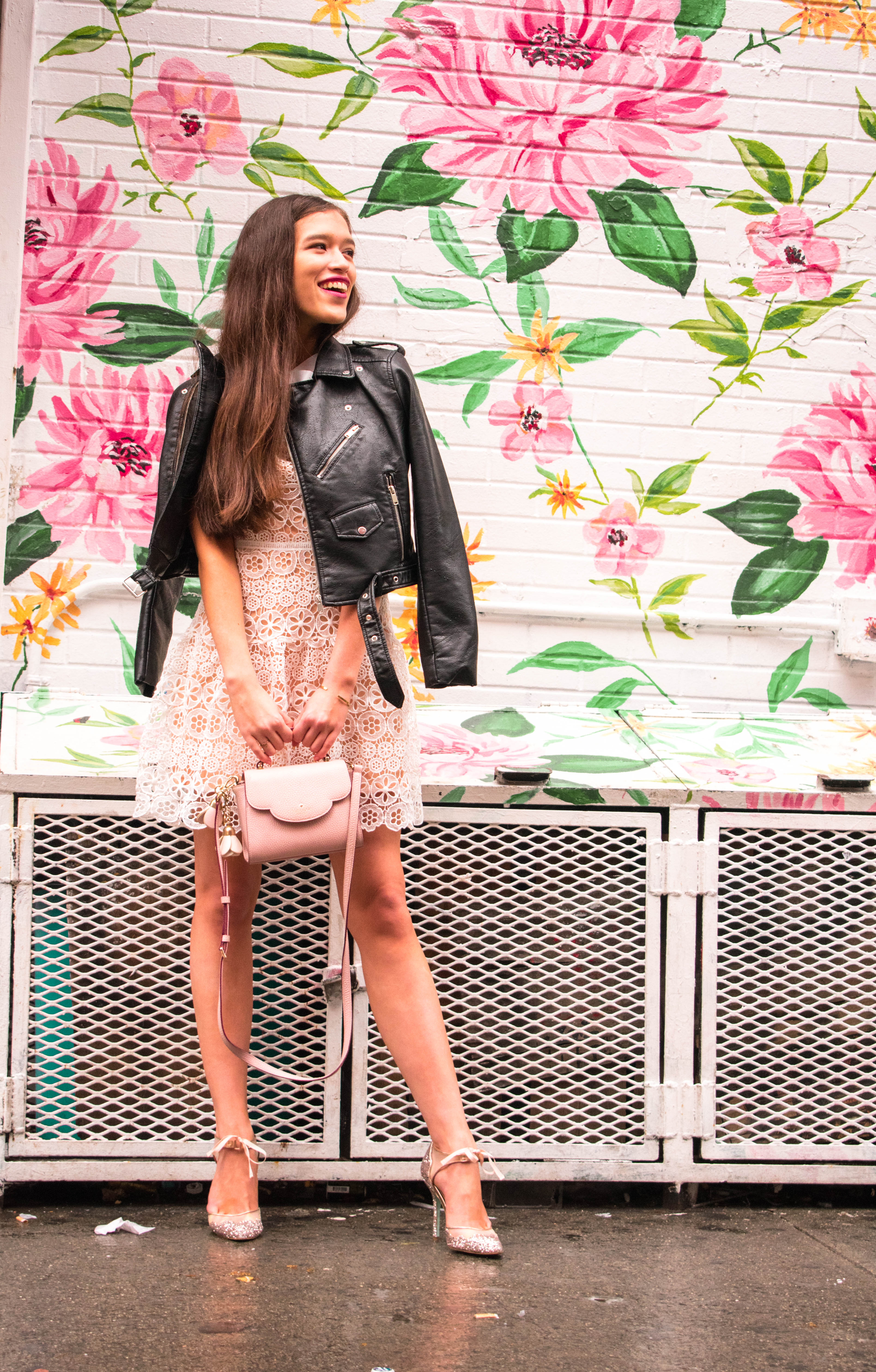 Style and travel blogger from NYC Eva Phan of Eva Darling in white Self Portrait lace fit and flare high neck dress with black leather motorcycle jacket vegan glitter stiletto stela betsey johnson heels yumi kim flower mural by surface of beauty kate spade mini makayla blush pink