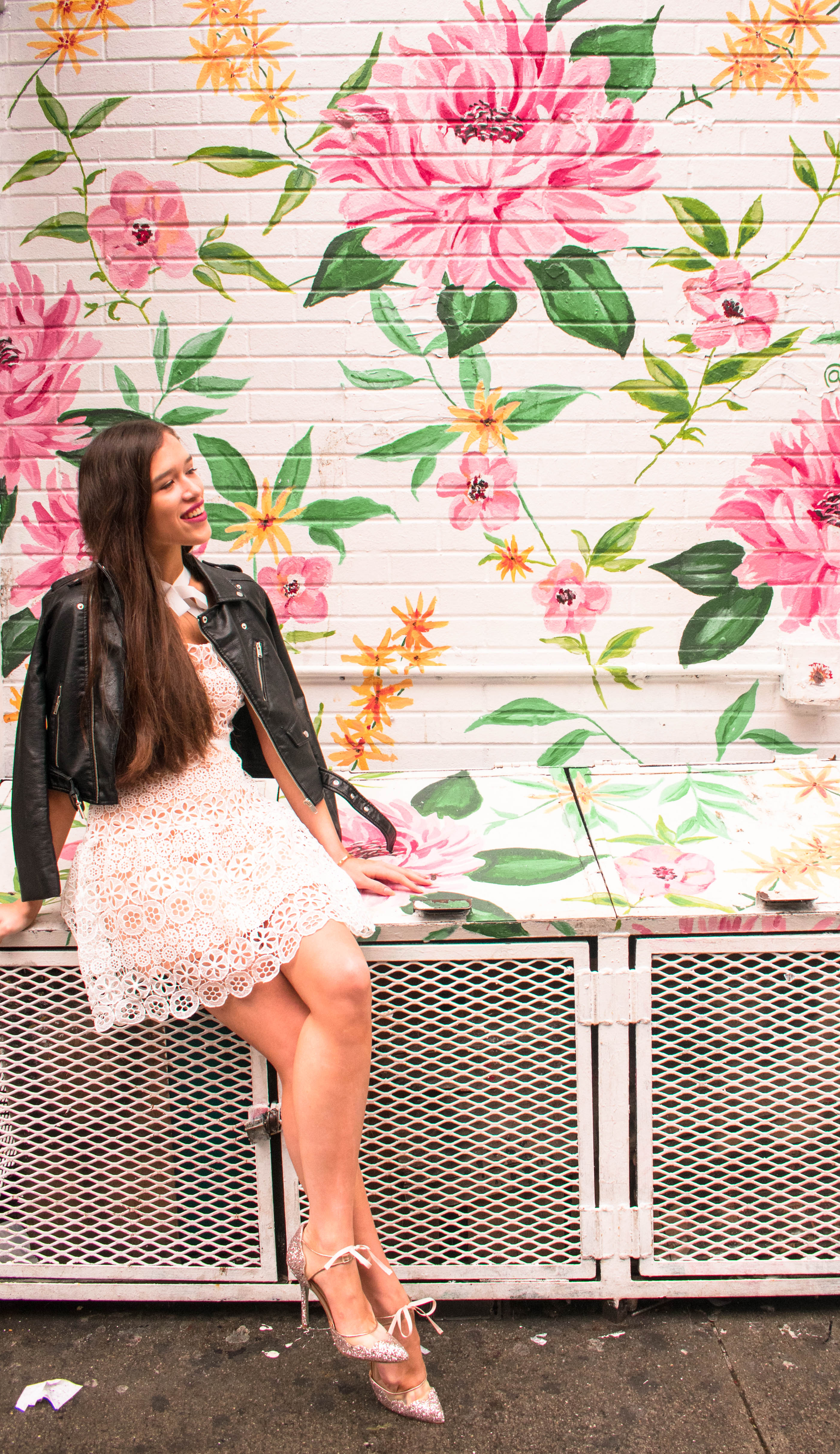 Style and travel blogger from NYC Eva Phan of Eva Darling sitting in white Self Portrait lace fit and flare high neck dress with black leather motorcycle jacket vegan glitter stiletto stela betsey johnson heels yumi kim flower mural by surface of beauty