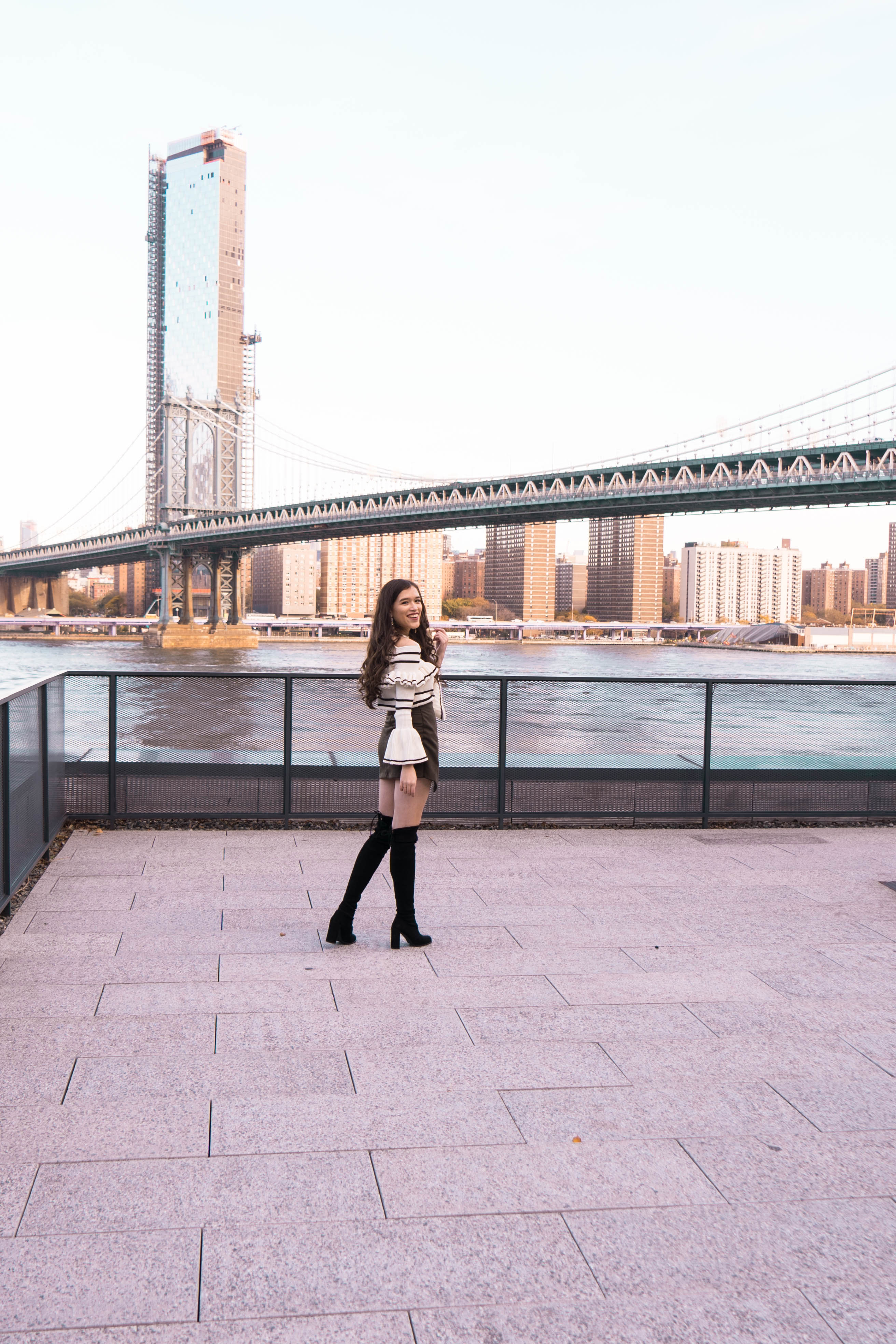 Popular NYC travel and style blogger Eva Phan of Eva Darling in DUMBO Brooklyn Manhattan skyline view roodtop World Trade Center Brooklyn Bridge self portrait bell sleeve sweater army green mini skirt black stuart weitzman hiline over the knee boots otk suede where to go in New York hidden public access rooftop free photography location trendy luxury teen ootd inspiration view of Manhattan Bridge