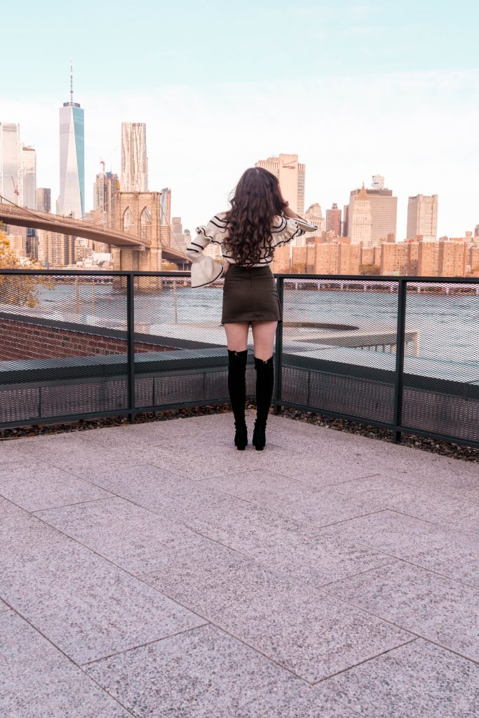 Popular NYC travel and style blogger Eva Phan of Eva Darling in DUMBO Brooklyn Manhattan skyline view roodtop World Trade Center Brooklyn Bridge self portrait bell sleeve sweater army green mini skirt black stuart weitzman hiline over the knee boots otk suede where to go in New York hidden public access rooftop free photography location