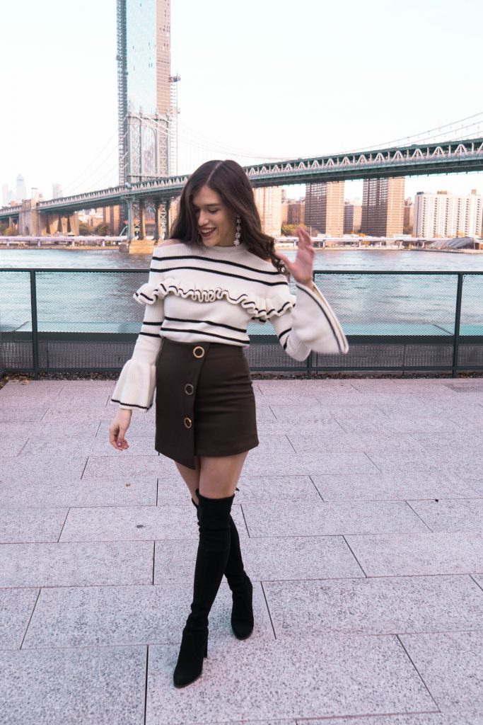 Popular NYC travel and style blogger Eva Phan of Eva Darling in DUMBO Brooklyn Manhattan skyline view roodtop World Trade Center Brooklyn Bridge self portrait bell sleeve sweater army green mini skirt black stuart weitzman hiline over the knee boots otk suede where to go in New York hidden public access rooftop free photography location trendy luxury teen ootd inspiration view of Manhattan Bridge how to style otk boots for winter