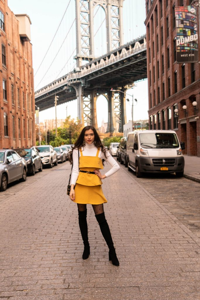 NYC style and fashion blogger in DUMBO Brooklyn thin skinny 1 inch gucci belt outfit with dress yellow ruffle stuart weitzman hiline black suede over the knee otk boots ootd inspo white turtleneck sweater prada astrology cahier black velvet handbag fall autumn cold weather feminine fashion lisi lerch emily pearl hoop earrings