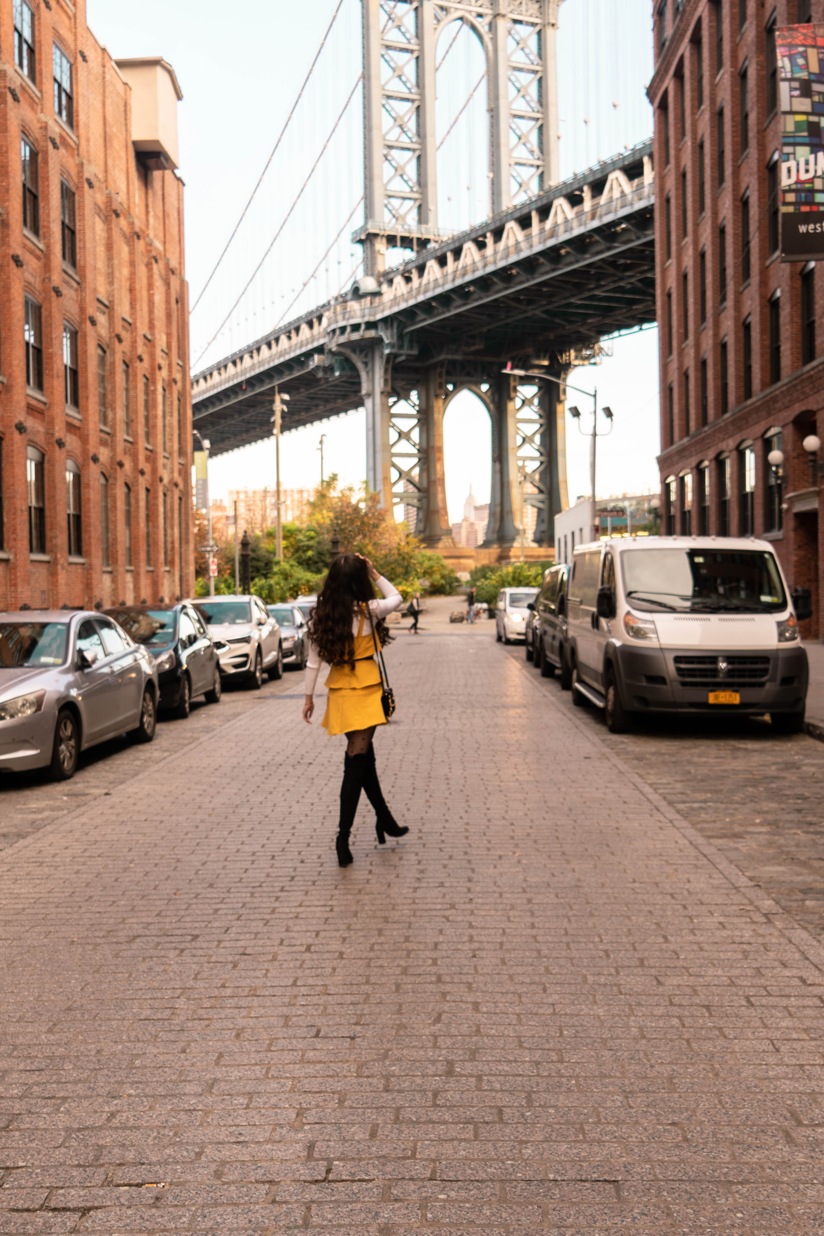 NYC style and fashion blogger in DUMBO Brooklyn thin skinny 1 inch gucci belt outfit with dress yellow ruffle stuart weitzman hiline black suede over the knee otk boots ootd inspo white turtleneck sweater prada astrology cahier black velvet handbag fall autumn cold weather feminine fashion lisi lerch emily pearl hoop earrings photo idea travel