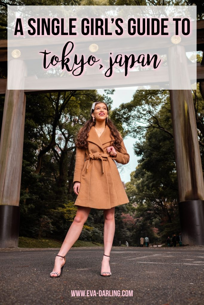 travel blogger Eva Phan of Eva Darling at the Meiji Jingu Shrine Shinto shrine in Harajuku Shibuya Tokyo Japan wearing a tan belted Michael Kords robe coat and black pearl strap stilettos long brown hair thick brunette hair curled pigtails traditional japanese architecture gateway minimalist style classic winter coat a single girl's guide to Tokyo, Japan solo female traveler asia