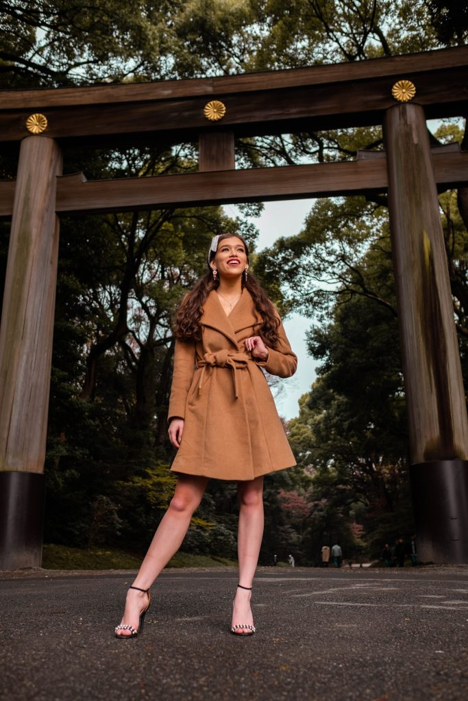travel blogger Eva Phan of Eva Darling at the Meiji Jingu Shrine Shinto shrine in Harajuku Shibuya Tokyo Japan wearing a tan belted Michael Kords robe coat and black pearl strap stilettos long brown hair thick brunette hair curled pigtails traditional japanese architecture gateway minimalist style classic winter coat