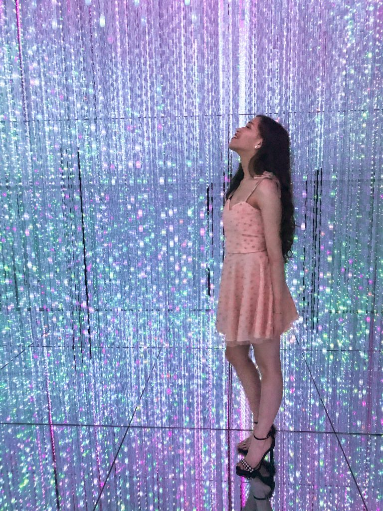 Travel and style blogger Eva Phan of Eva Darling at teamLab Borderless Mori Digital Art Building Museum in Tokyo Japan long brown curled hair light installation wearing Eva Phan Collection flattering fit and flare dress