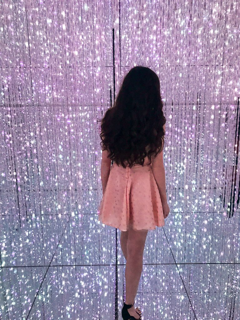 Travel and style blogger Eva Phan of Eva Darling at teamLab Borderless Mori Digital Art Building Museum in Tokyo Japan long brown curled hair light installation