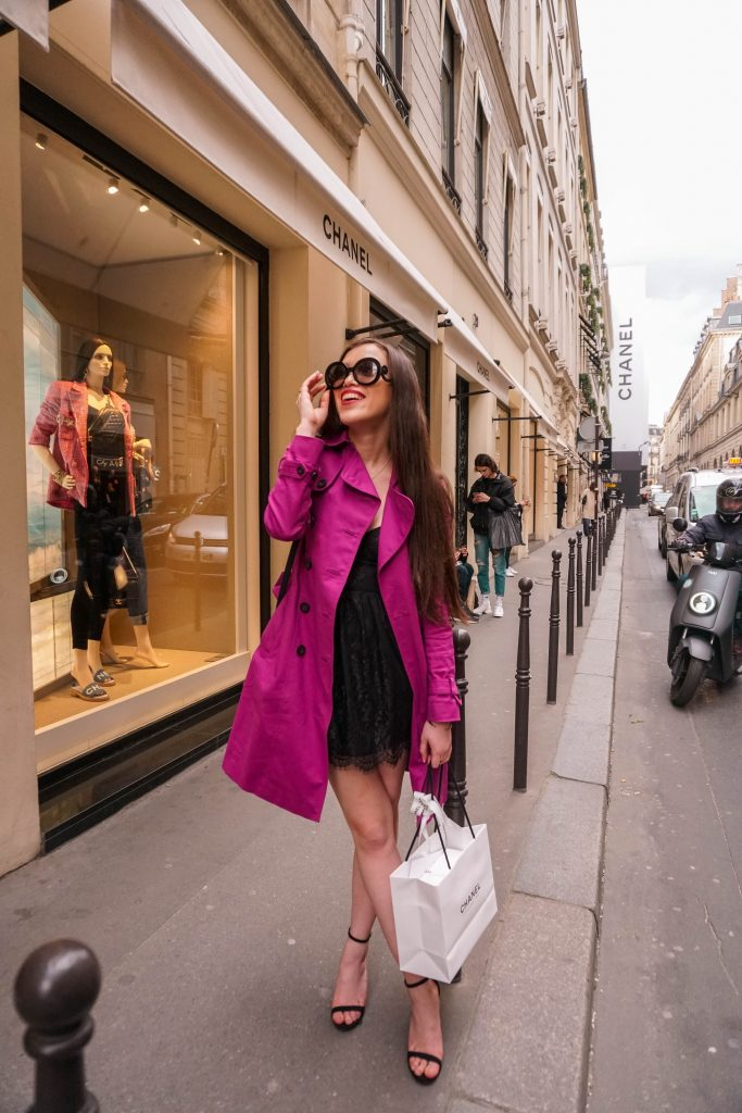 Eva Darling at the Chanel flagship store on Rue Cambon wearing a black lace dress from Revolve, magenta hobbs trench coat, black loveliness stilettos from Lulus in Paris France Prada Baroque Sunglasses