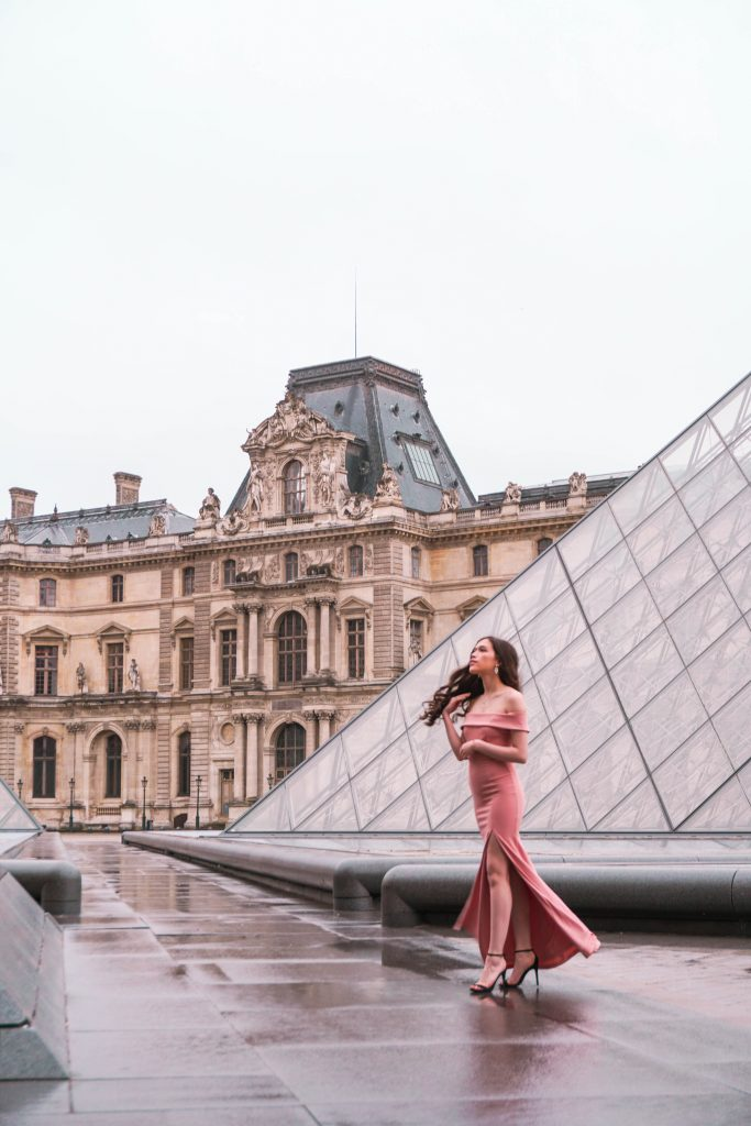 Eva Phan of Eva Darling Louvre Museum Musée du Louvre glass pyramids Paris France Lulu's Mauve Aveline Gown off the shoulder column mermaid dress Loveliness black suede stiletto heel Paris photoshoot photo shoot location idea feminine style