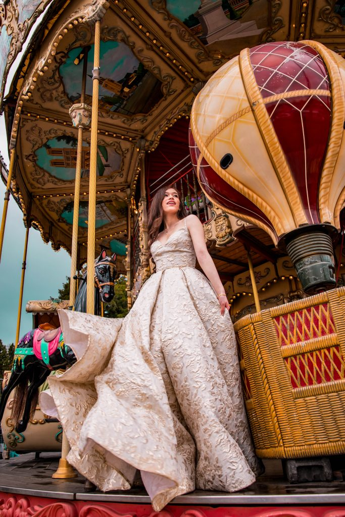 Eva Phan of Eva Darling wearing a Tarik Edix Ballgown at the eiffel tower carousel carrousel de la tour eiffel in place du trocadeo paris france paris photo inspiration photoshoot idea feminine style whimsical travel luxury fashion outfit long brown hair curled