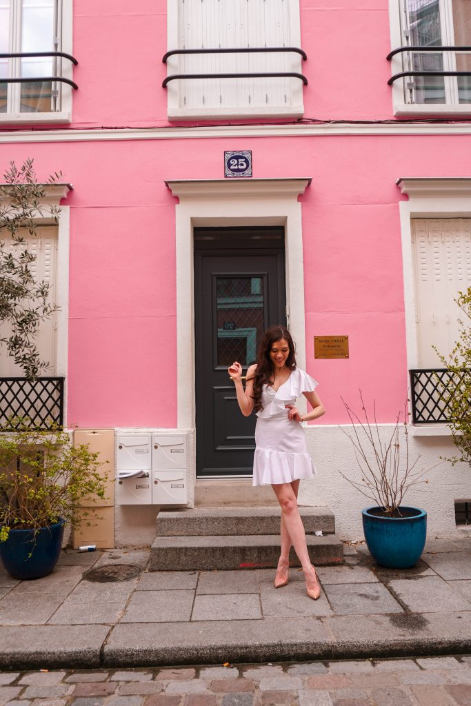style blogger Eva Phan of Eva Darling on rue cremieux in paris france most instagram worthy instagrammable road in Paris best spot for a photo in france white amanda uprichard vanderbilt dress christian louboutin hot chick pumps in nude pink wall in paris instagram location