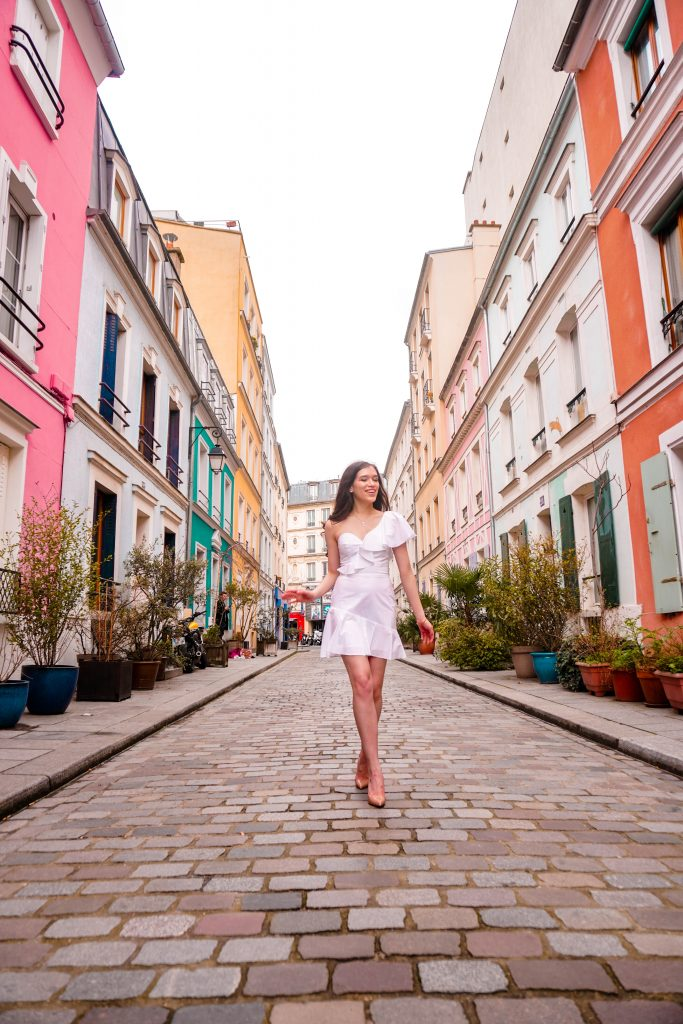 Eva Phan Eva Darling Rue Cremieux Paris France most instagram worthy road bright colored houses pastel pink instagrammable spot white amanda uprichard vanderbilt dress christian loubouting hot chick nude shoes feminine women's fashion long brown curled hair where to go in paris travel guide idea europe