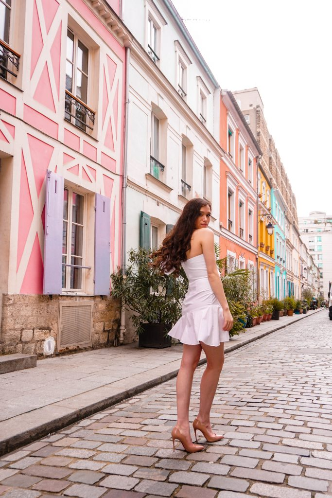 Eva Phan Eva Darling Rue Cremieux Paris France most instagram worthy road bright colored houses pastel pink instagrammable spot white amanda uprichard vanderbilt dress christian loubouting hot chick nude shoes feminine women's fashion long brown curled hair where to go in paris spring fashion white party dress idea