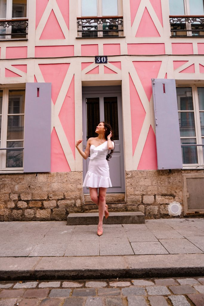 style blogger Eva Phan of Eva Darling on rue cremieux in paris france most instagram worthy instagrammable road in Paris best spot for a photo in france white amanda uprichard vanderbilt dress christian louboutin hot chick pumps in nude parisian style pink house