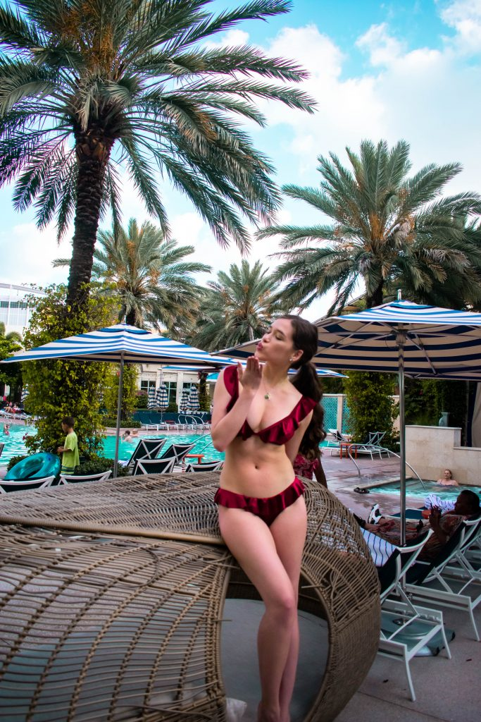 Travel blogger Eva Darling at the Hilton West Palm Beach pool velvet ruffle bikini inexpensive swimwear vacation florida blowing a kiss