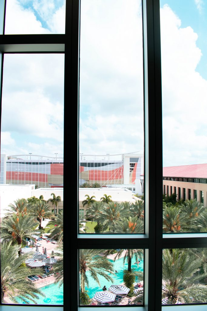 floor to ceiling windows with a view of the pool at the Hilton West Palm Beach Hotel