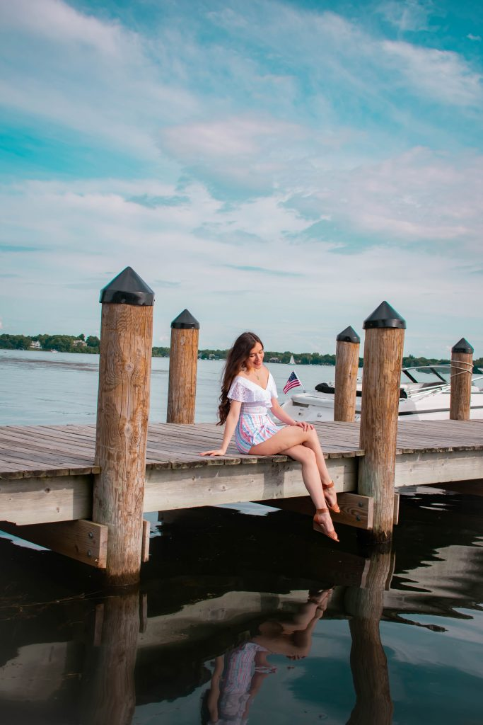 Eva Phan of Eva Darling xoxo clothing trendy summer outfit inexpensive college girl style white lace bodysuit red white and blue striped mini skort lake minnetonka wayzata minnesota comfortable summer brown wedge sandals style travel blogger