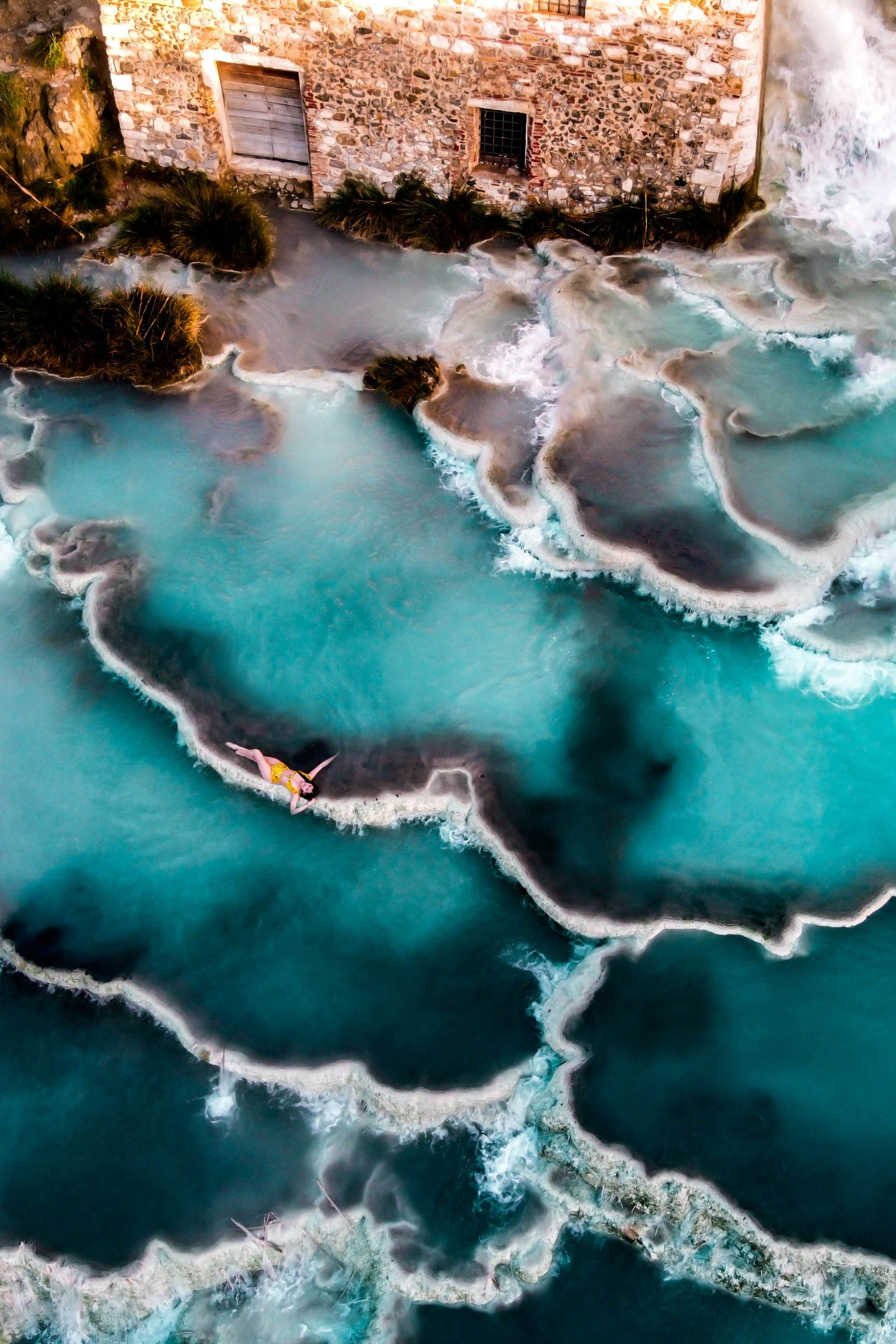 eva phan cascate del mulino terme di saturnia natural hot springs tuscany thermal bath spa italy solo female travel province of grosseto italy where to go tuscany dji mavic mini drone photography shein inexpensive yellow high waisted bikini wanderlust travel inspo