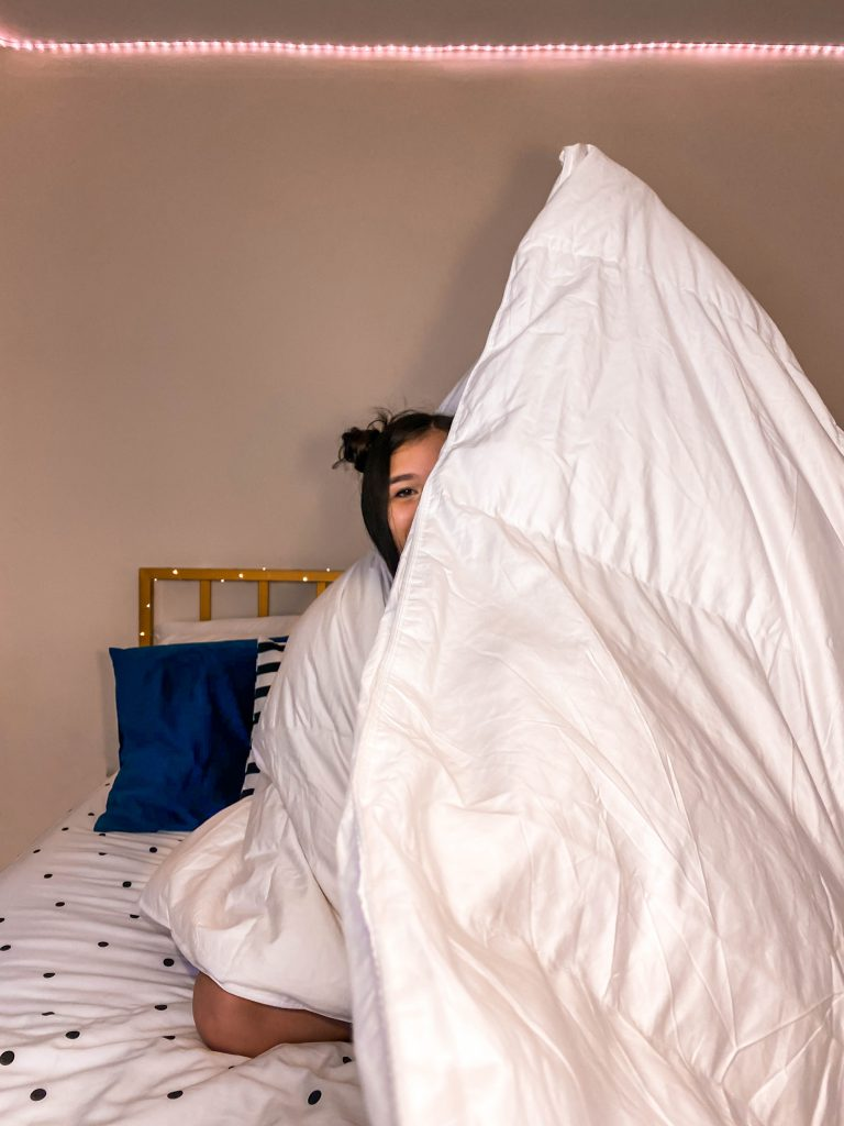 brunette space buns in bed white king size down duvet inexpensive affordable home depot