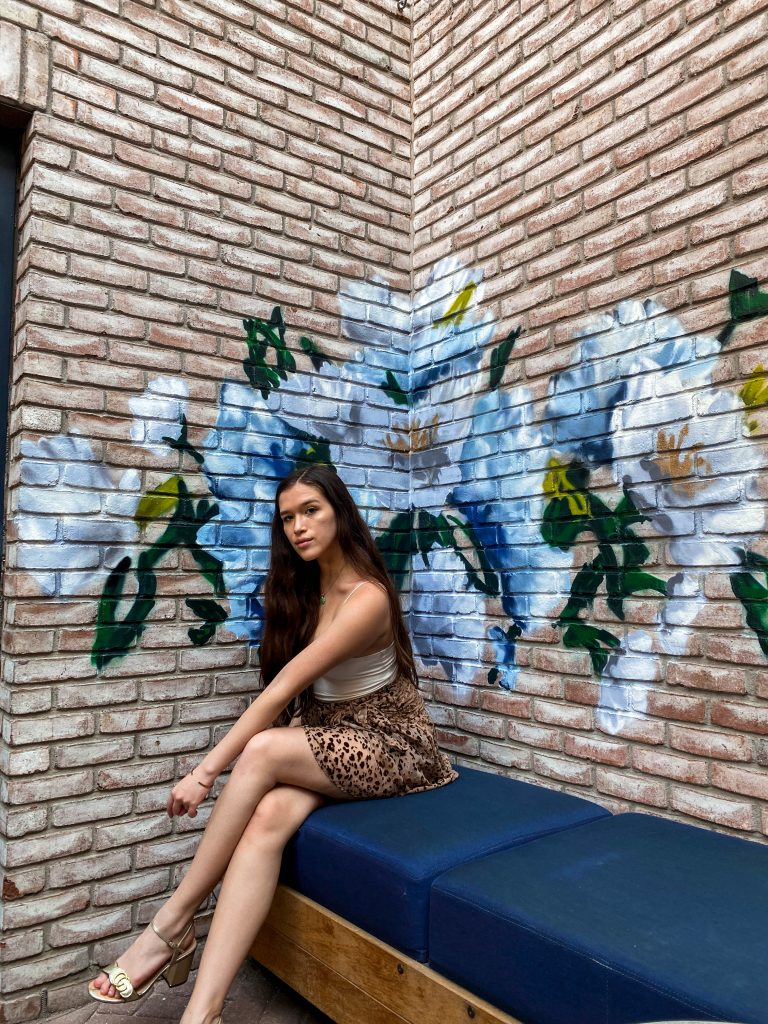 ashley joon art floral painting instagrammable rooftop bar death and co the garden ramble hotel denver colorado photo location girl brunette long straight hair sitting haute hippie cheetah wrap skirt gucci marmont gold metallic block chunky heels