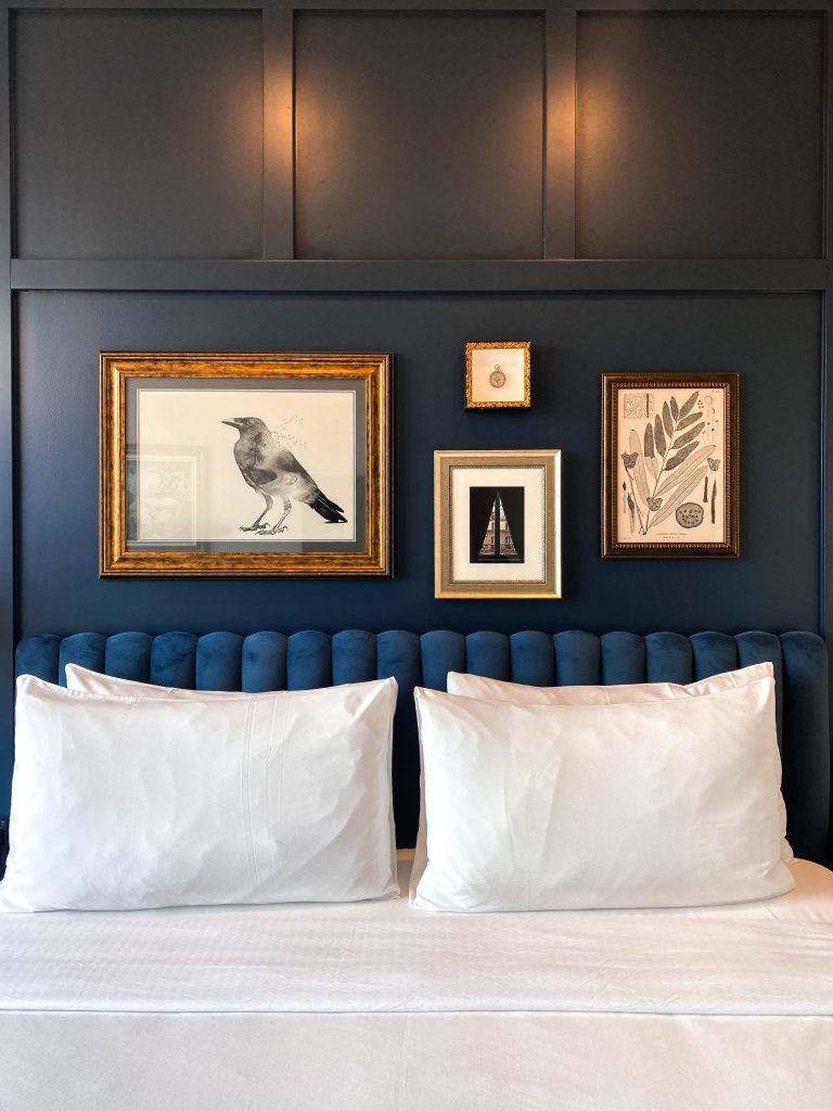 the ramble hotel rino denver king room blue wall vintage gallery wall luxury boutique hotel colorado