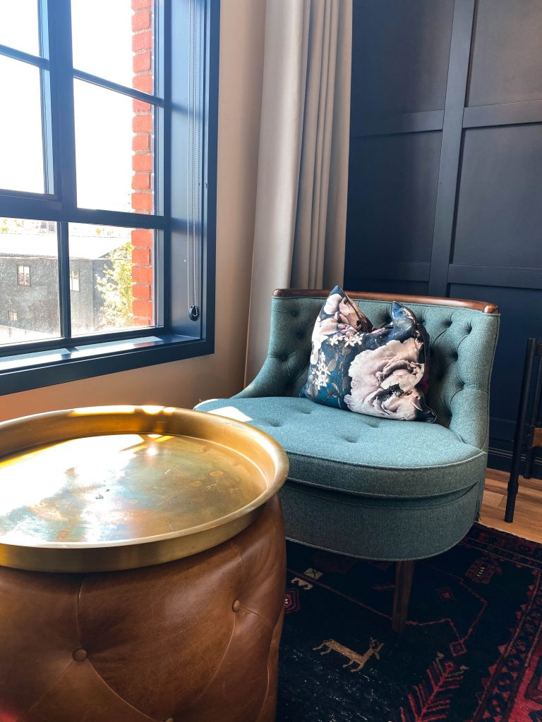 teal tufted sitting chair floral pillow denver luxury boutique hotel