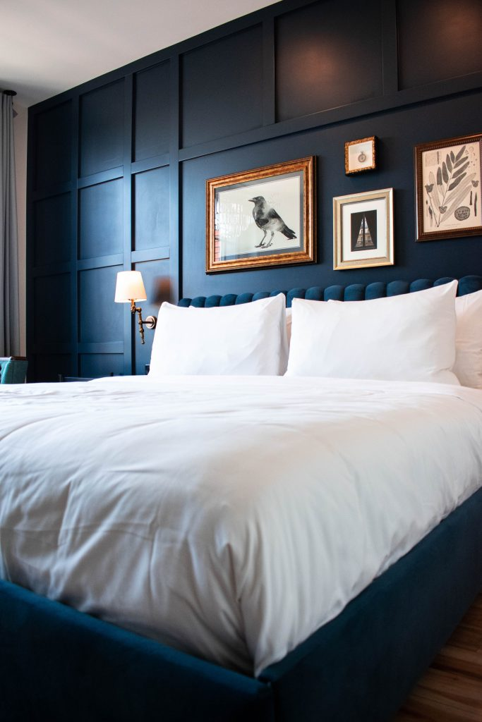 the ramble hotel rino denver king room blue wall vintage gallery wall luxury boutique hotel colorado king size bed mattress white bedding